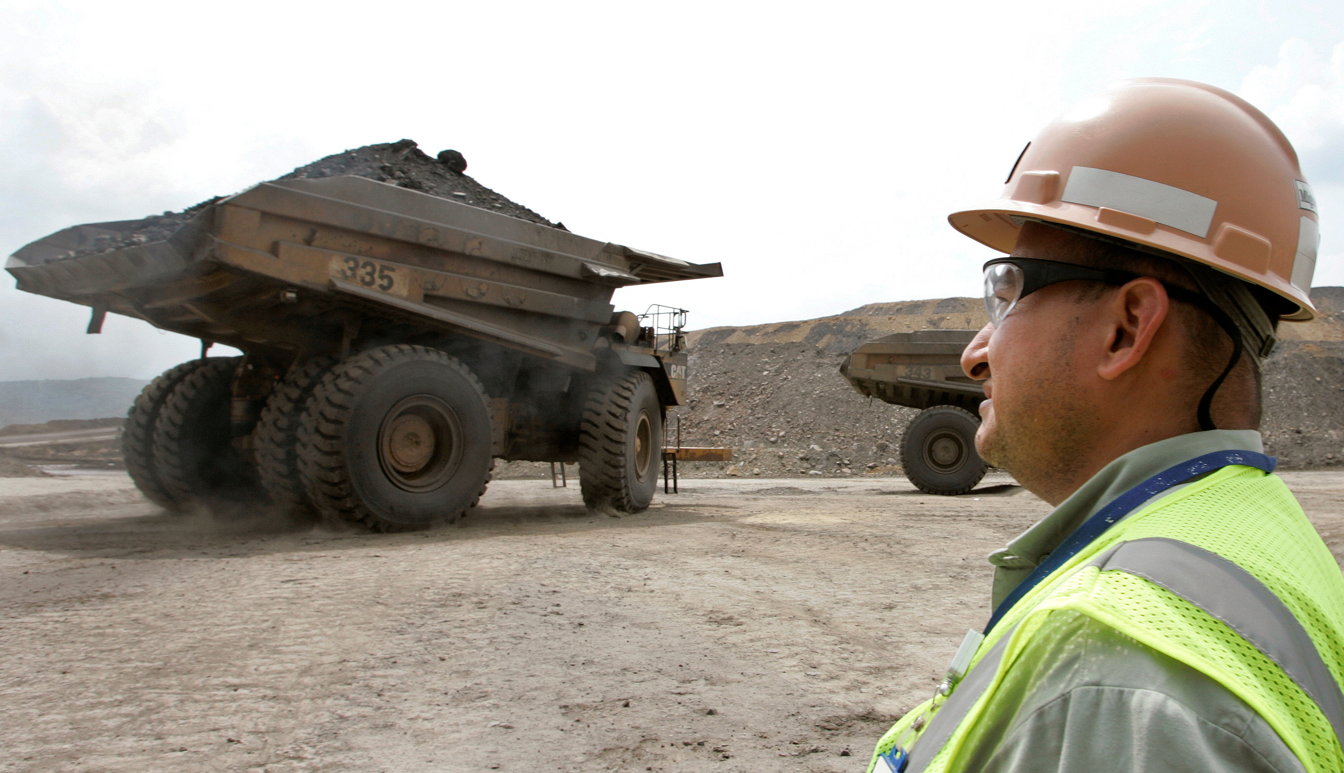 A Colombian worker looks as a mining truck drives away at the Cerrejon coal mine near Barrancas, Guajira province, May 24, 2007. Picture taken on May 24, 2007  REUTERS/Jose Miguel Gomez/File Photo
