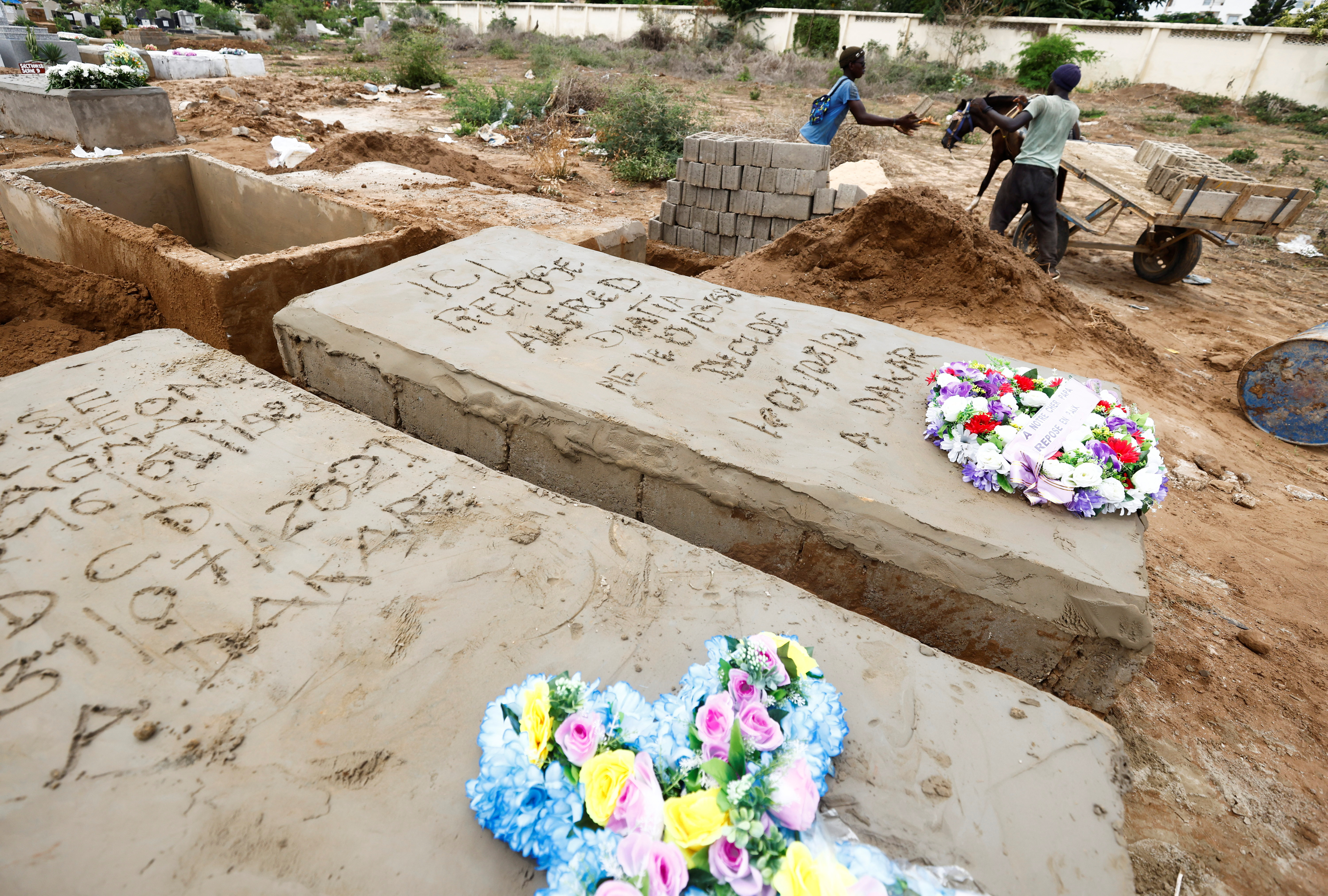 Grave diggers offload bricks next to the grave of a man who, according to his son, died from the coronavirus disease (COVID-19), at the Christian Saint-Lazare Cemetery, as Senegal records more COVID-19 deaths, Dakar, Senegal August 4, 2021. REUTERS/Zohra Bensemra
