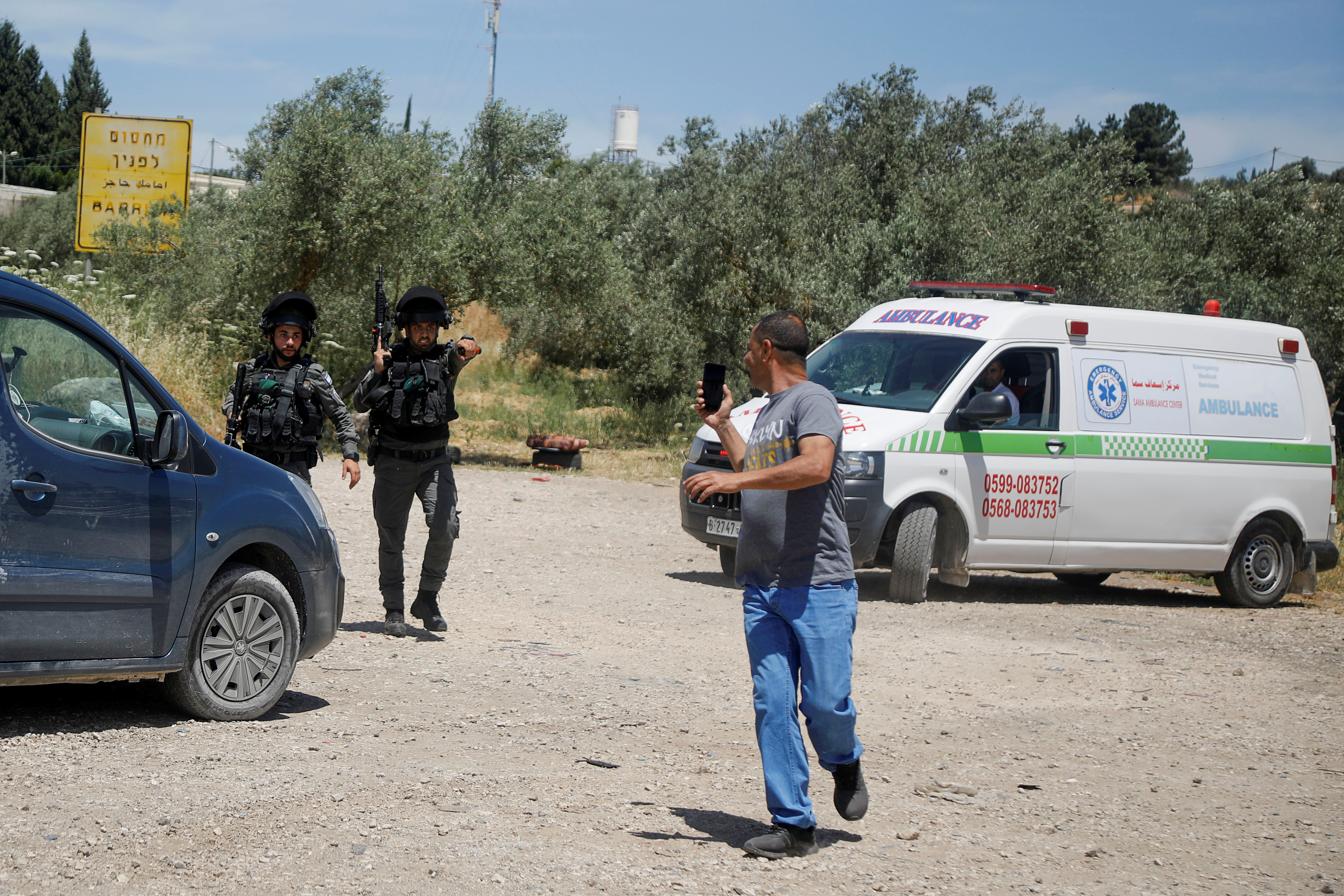 A Palestinian man uses his mobile to film Israeli border police members near the scene of a security incident at an Israeli military base near Jenin in the Israeli-occupied West Bank, May 7, 2021. REUTERS/Raneen Sawafta