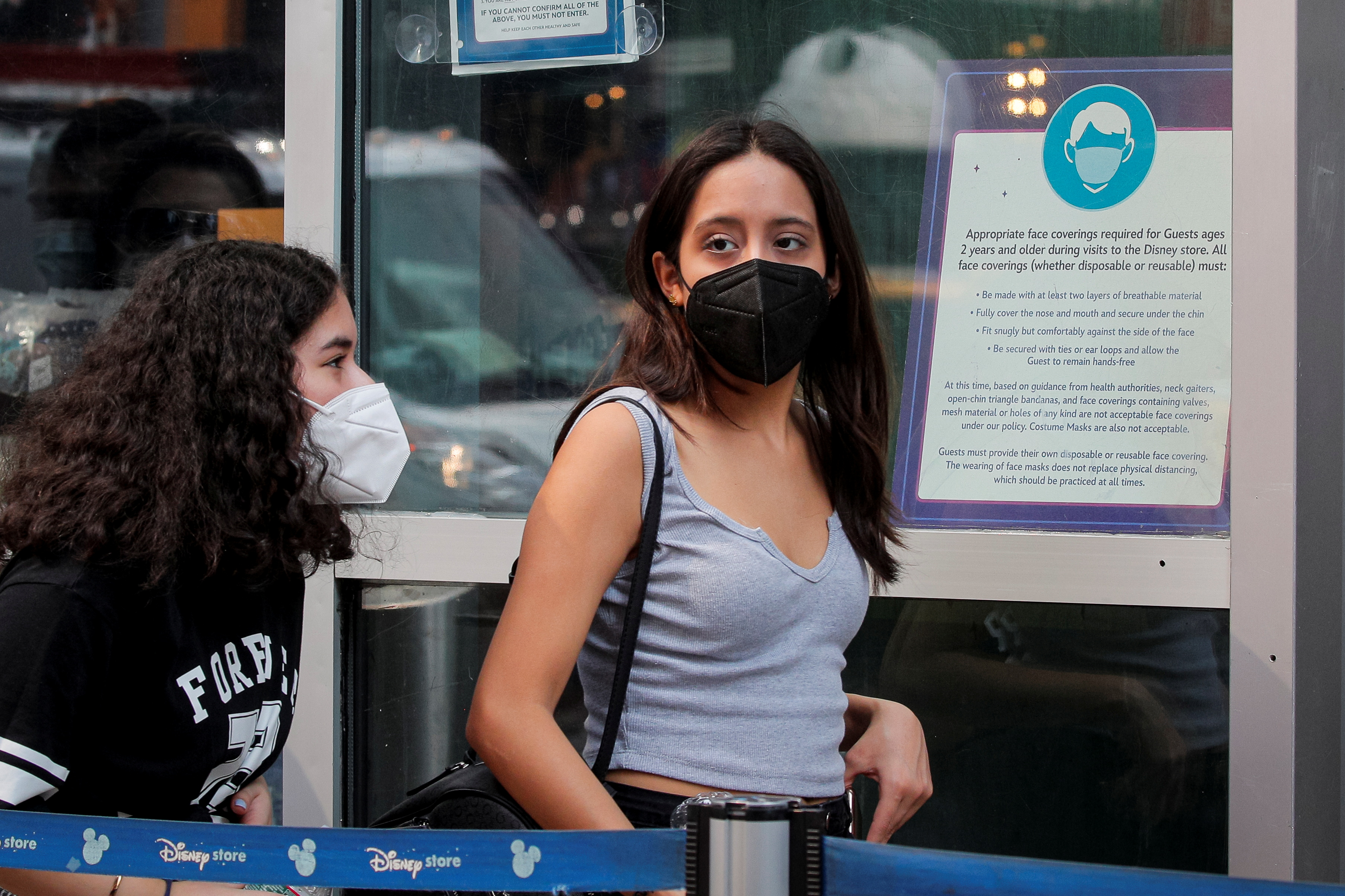 People wear masks against the coronavirus disease (COVID-19), following the CDC recommendation that fully vaccinated Americans wear masks as the highly transmissible Delta variant has led to a surge in infections, as they enter the Disney Store in Times Square in New York City, New York, U.S., July 27, 2021. REUTERS/Brendan McDermid