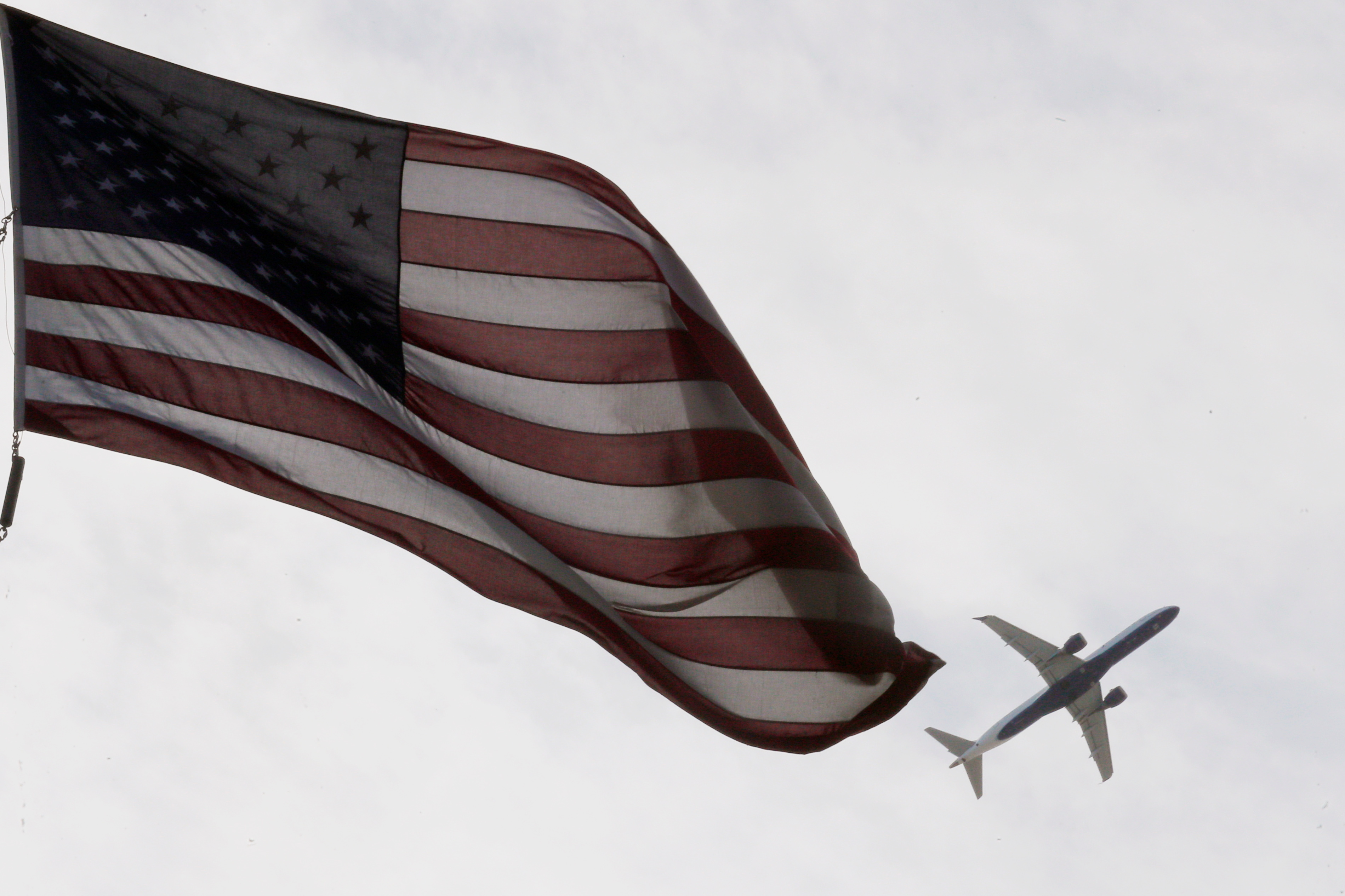 A Delta Airlines flight takes off past a U.S. flag in Boston, Massachusetts, U.S., May 27, 2021.   REUTERS/Brian Snyder