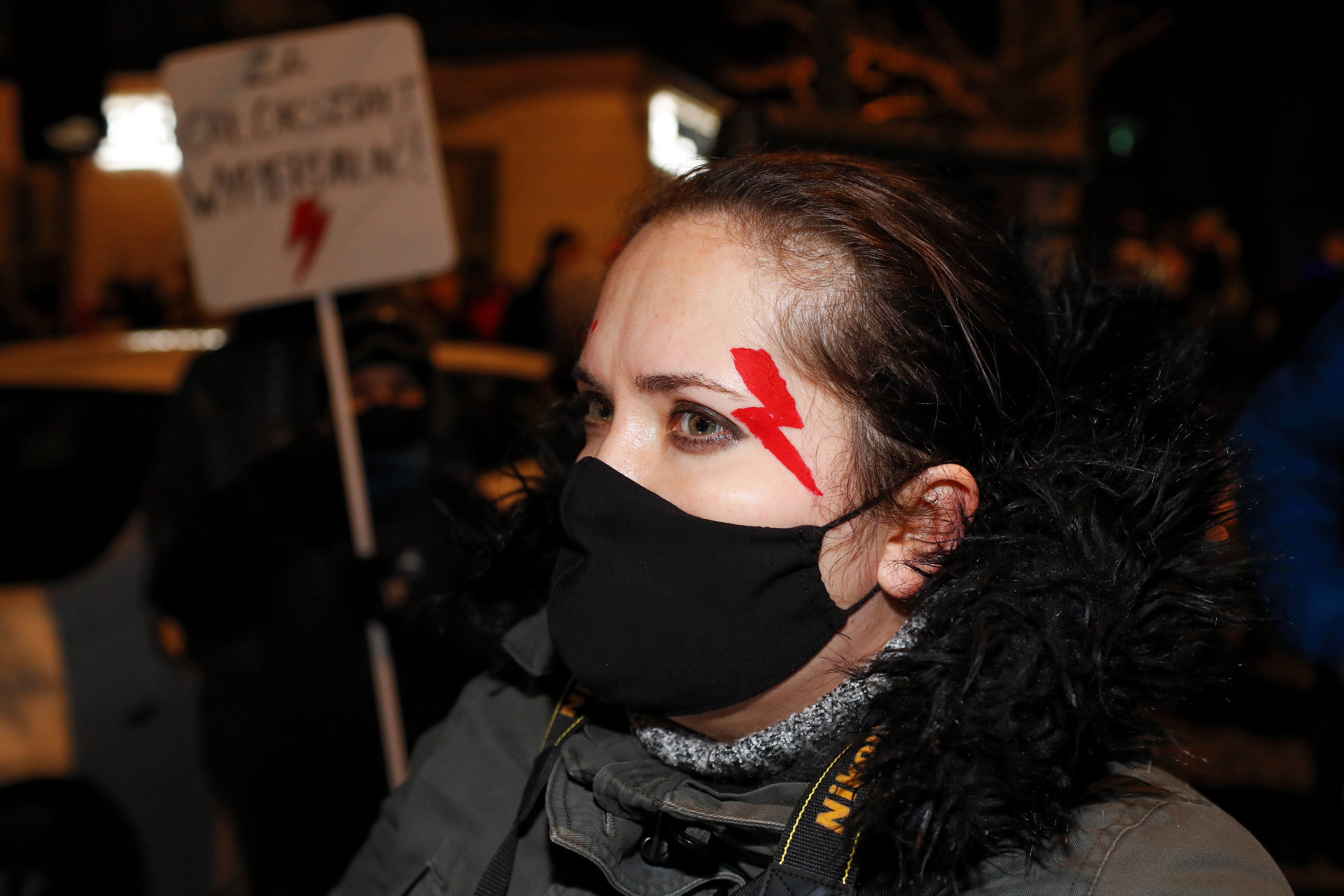 A demonstrator with a red lightning bolt on her face attends a protest against verdict restricting abortion rights in Warsaw, Poland, January 27, 2021. REUTERS/Kacper Pempel