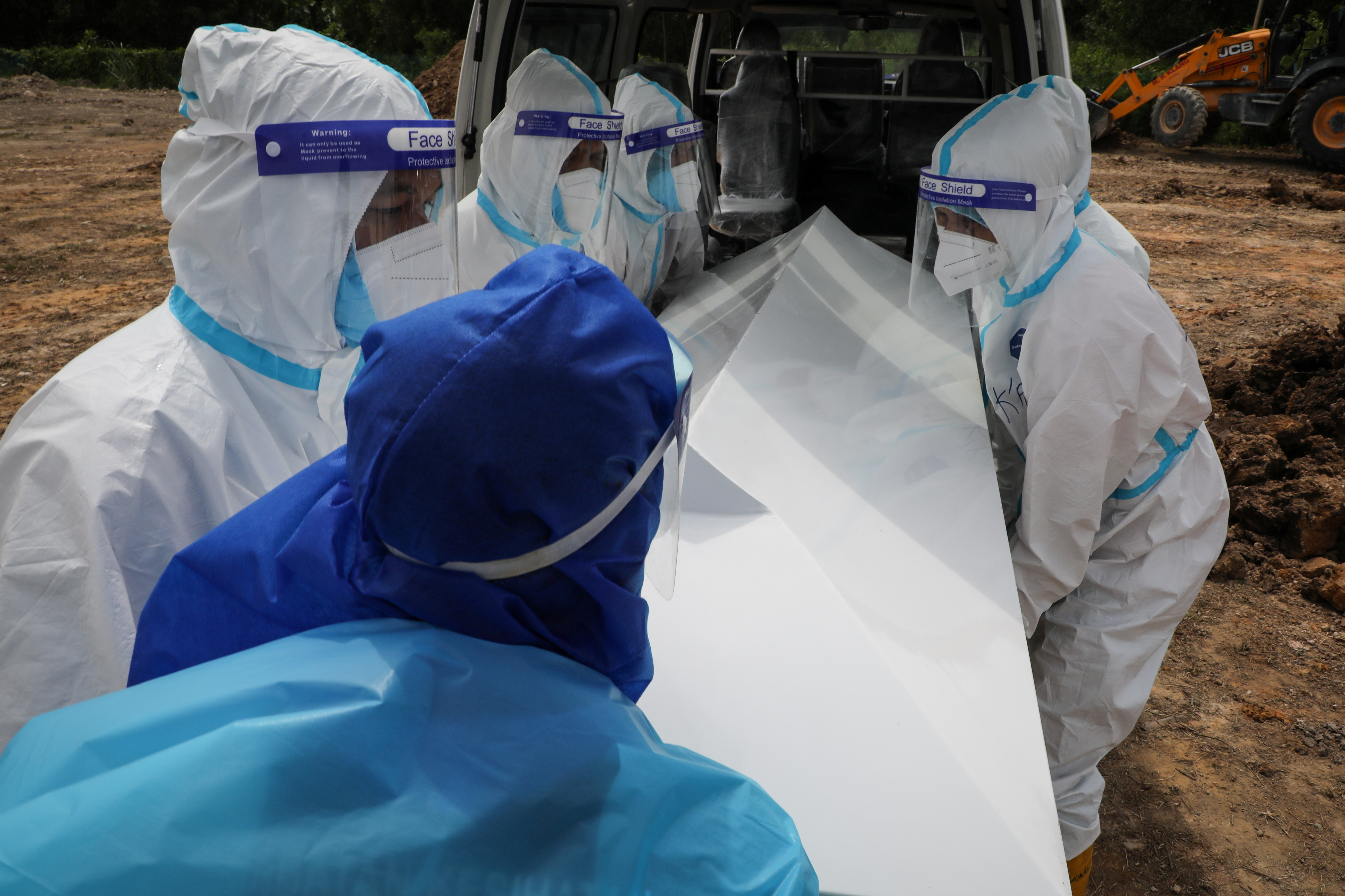 Cemetery workers wearing protective suits carry the body of a coronavirus disease (COVID-19) victim at a cemetery in Klang, Malaysia July 24, 2021. REUTERS/Lim Huey Teng