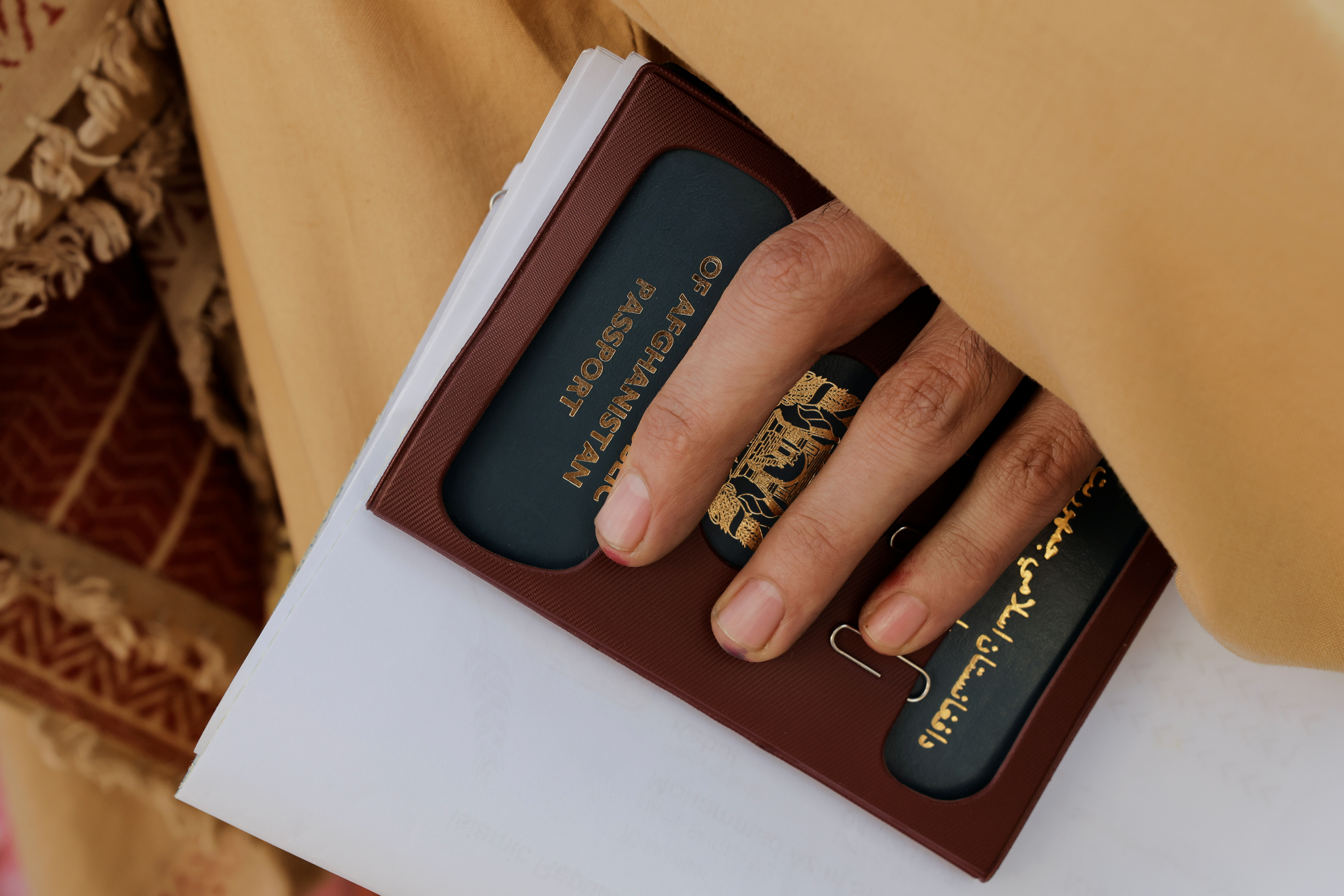 A man holds an expired passport as Afghans gather outside the passport office after Taliban officials announced they will start issuing passports to its citizens again, following months of delays that hampered attempts by those trying to flee the country after the Taliban seized control, in Kabul, Afghanistan October 6, 2021. REUTERS/Jorge Silva