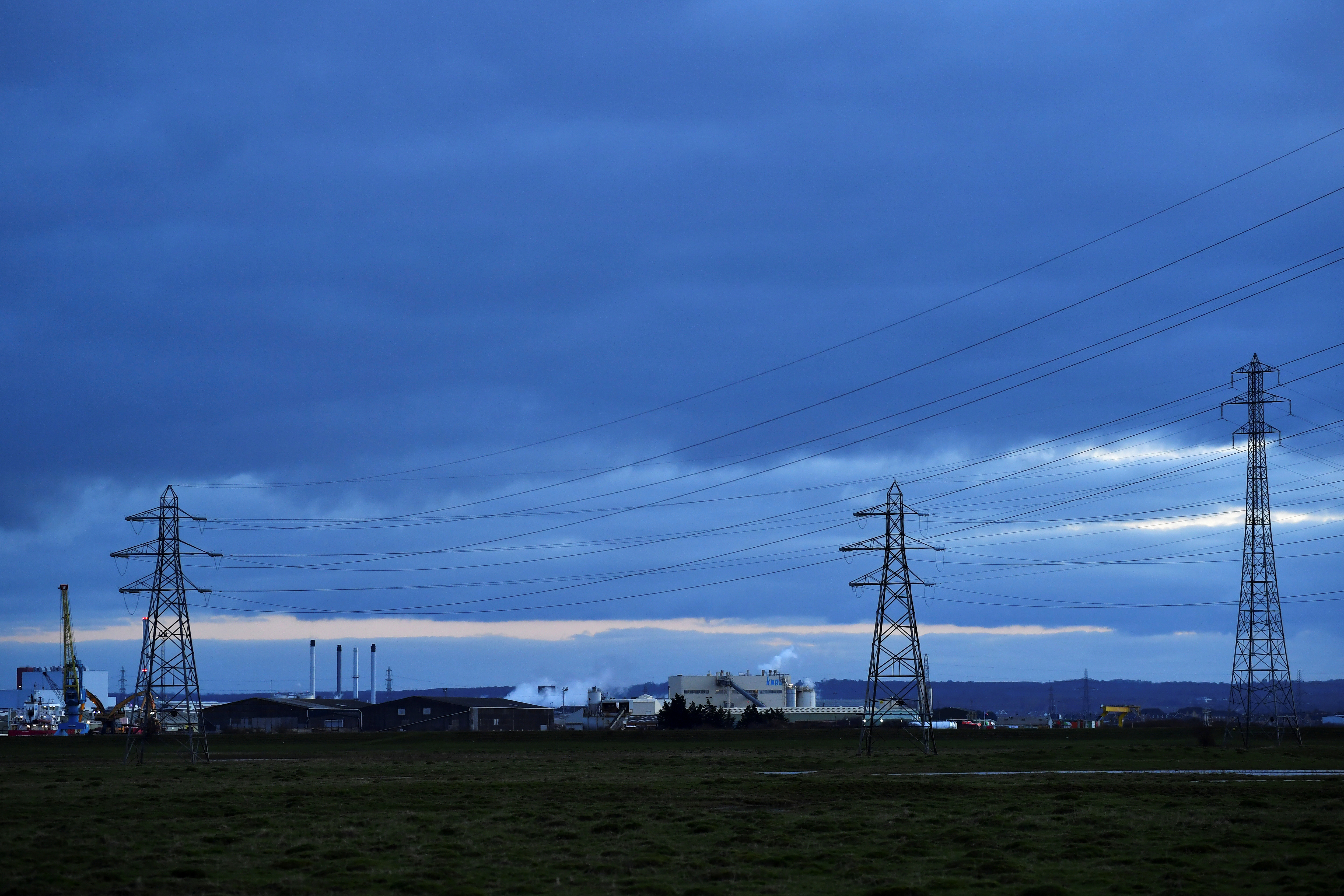 A factory and electricity pylons are seen from Sheerness, on the Isle of Sheppey, Britain, March 5, 2021. Picture taken March 5, 2021.  To match Special Report HEALTH-CORONAVIRUS/UK-VARIANT  REUTERS/Dylan Martinez