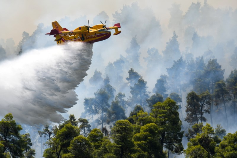 A firefighting airplane makes a water drop as a wildfire burns near the village of Ellinika, on the island of Evia, Greece, August 8, 2021. REUTERS/Alexandros Avramidis