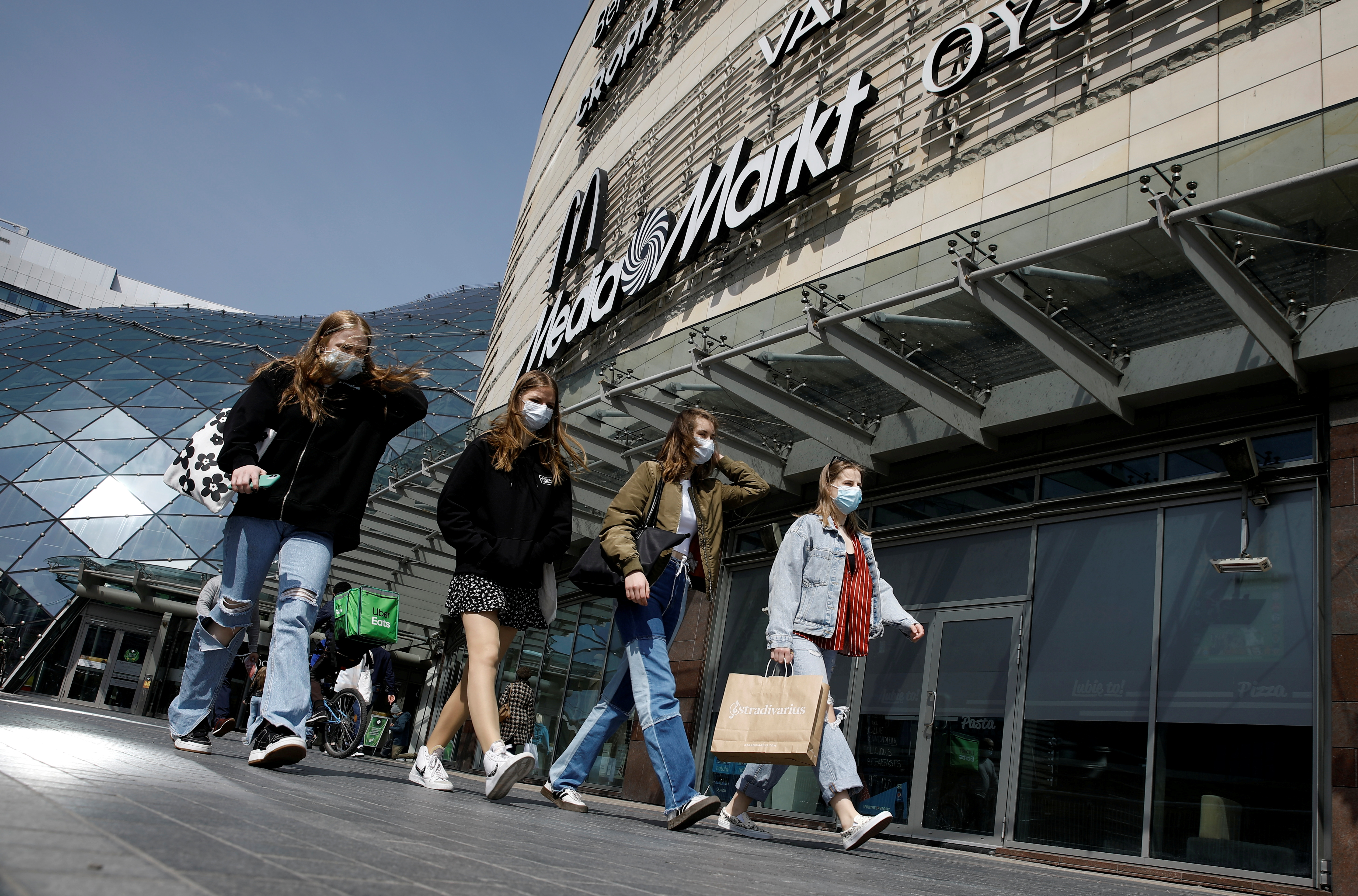 People wearing protecting masks walk in front of the Zlote Tarasy shopping mall in the centre of the city as the government eased coronavirus disease (COVID-19) restrictions, in Warsaw, Poland May 4, 2021. REUTERS/Kacper Pempel