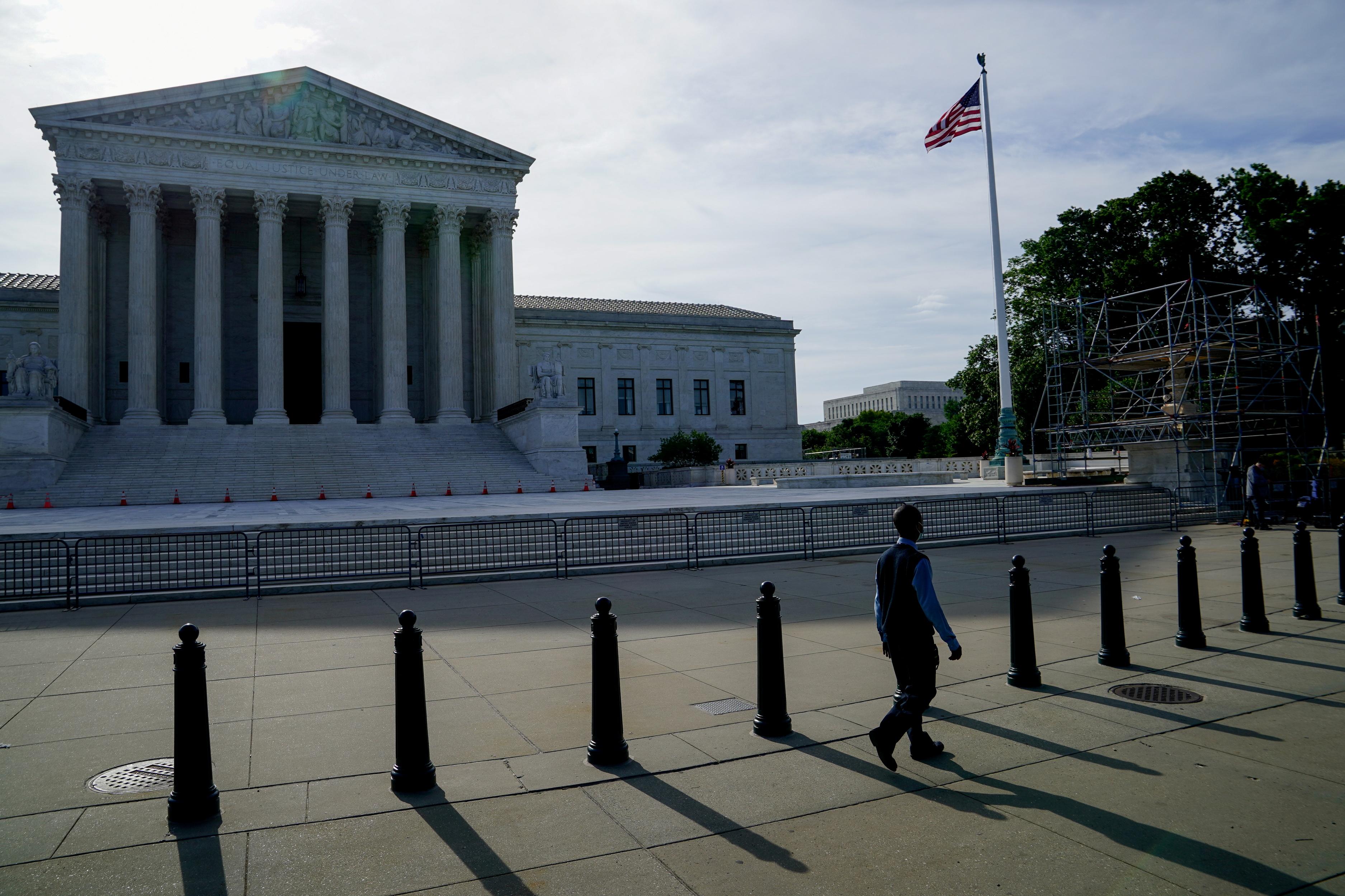 People walk past the U.S. Supreme Court in Washington, U.S., June 1, 2021. REUTERS/Erin Scott