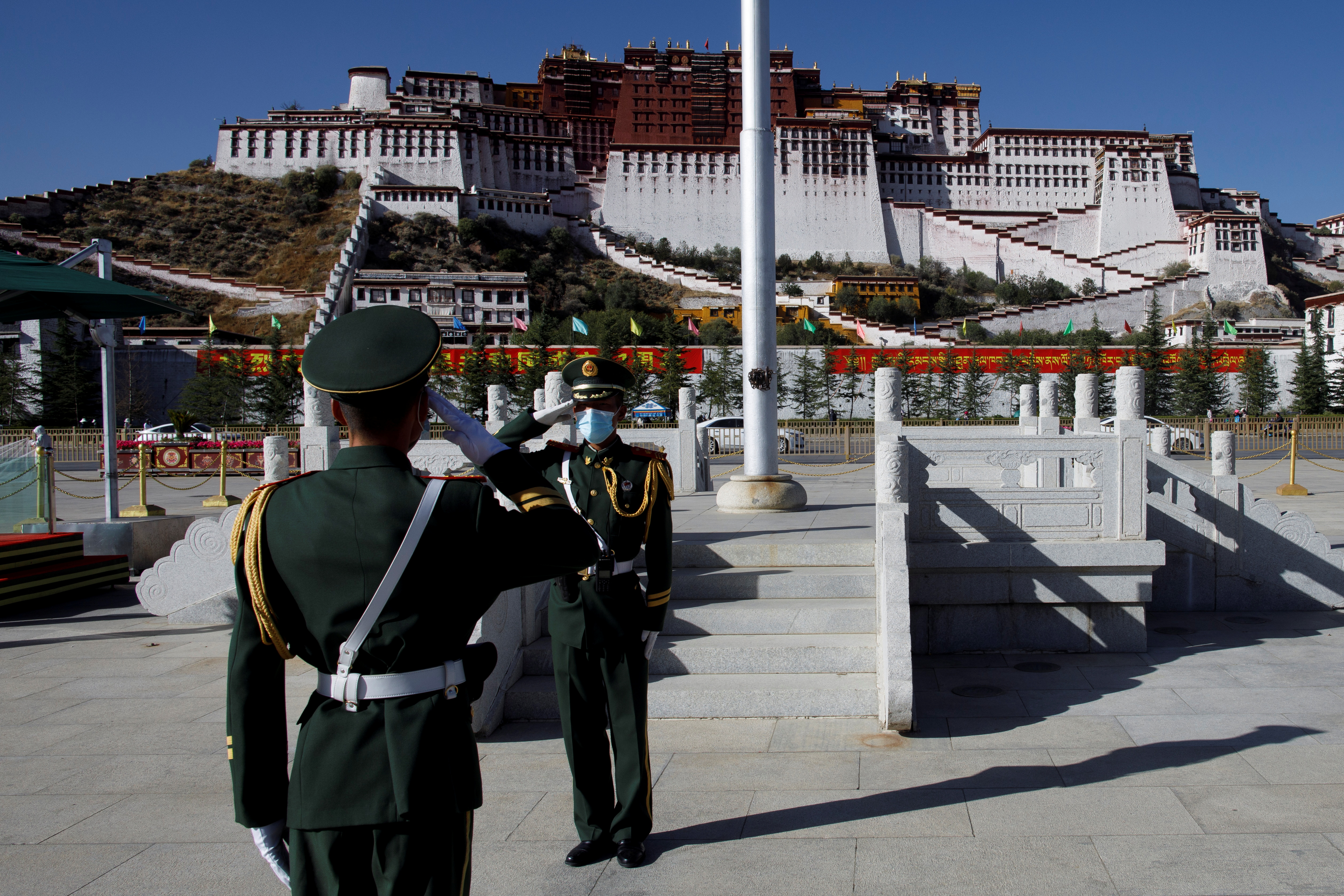 Paramilitary police officers salute during a change of flag duty in front of Potala Palace in Lhasa during a government-organised tour of the Tibet Autonomous Region, China, October 15, 2020.  Picture taken October 15, 2020.  REUTERS/Thomas Peter