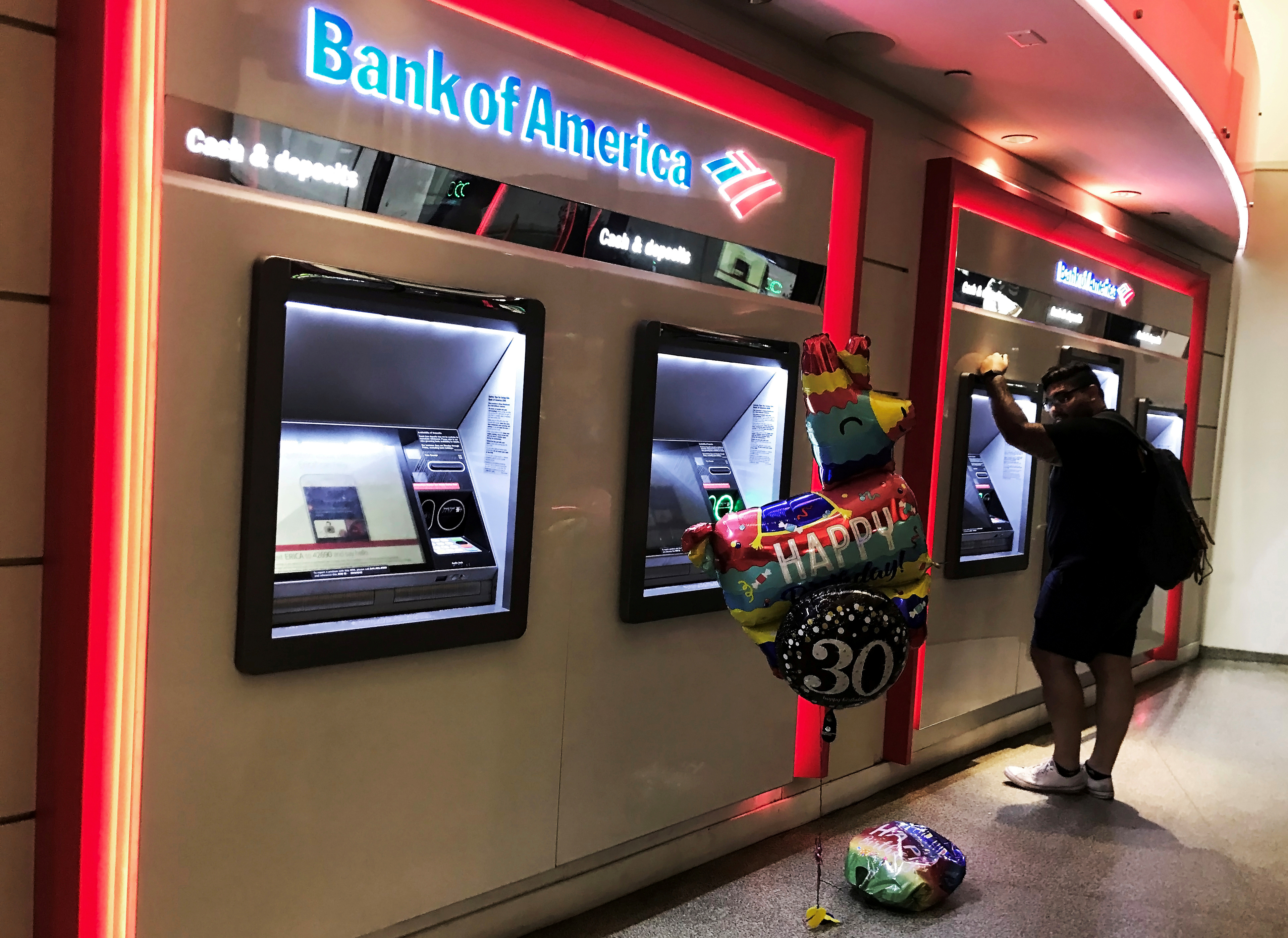 A man uses an ATM machine next an inflatable plastic balloon inside a Bank of America branch in Times Square in New York, U.S., August 10, 2019. REUTERS/Nacho Doce/File Photo