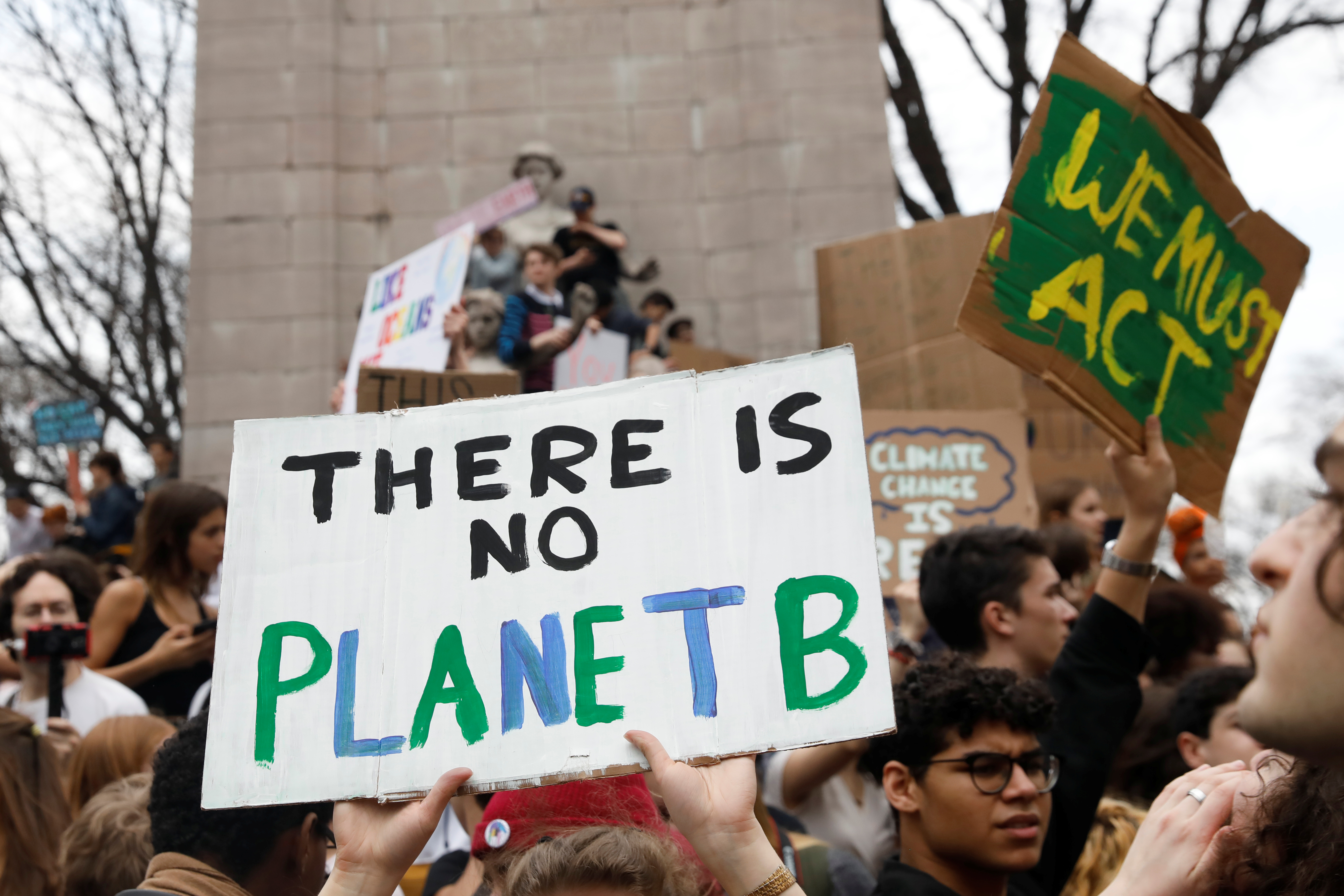 Students hold placards during a demonstration against climate change. REUTERS/Shannon Stapleton