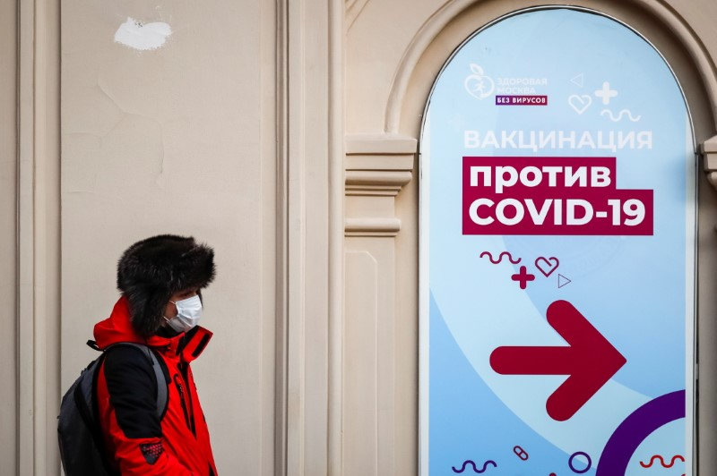A man walks past a sign outside a vaccination centre in the State Department Store, GUM, amid the outbreak of the coronavirus disease (COVID-19), in central Moscow, Russia January 18, 2021 REUTERS/Shamil Zhumatov/File Photo