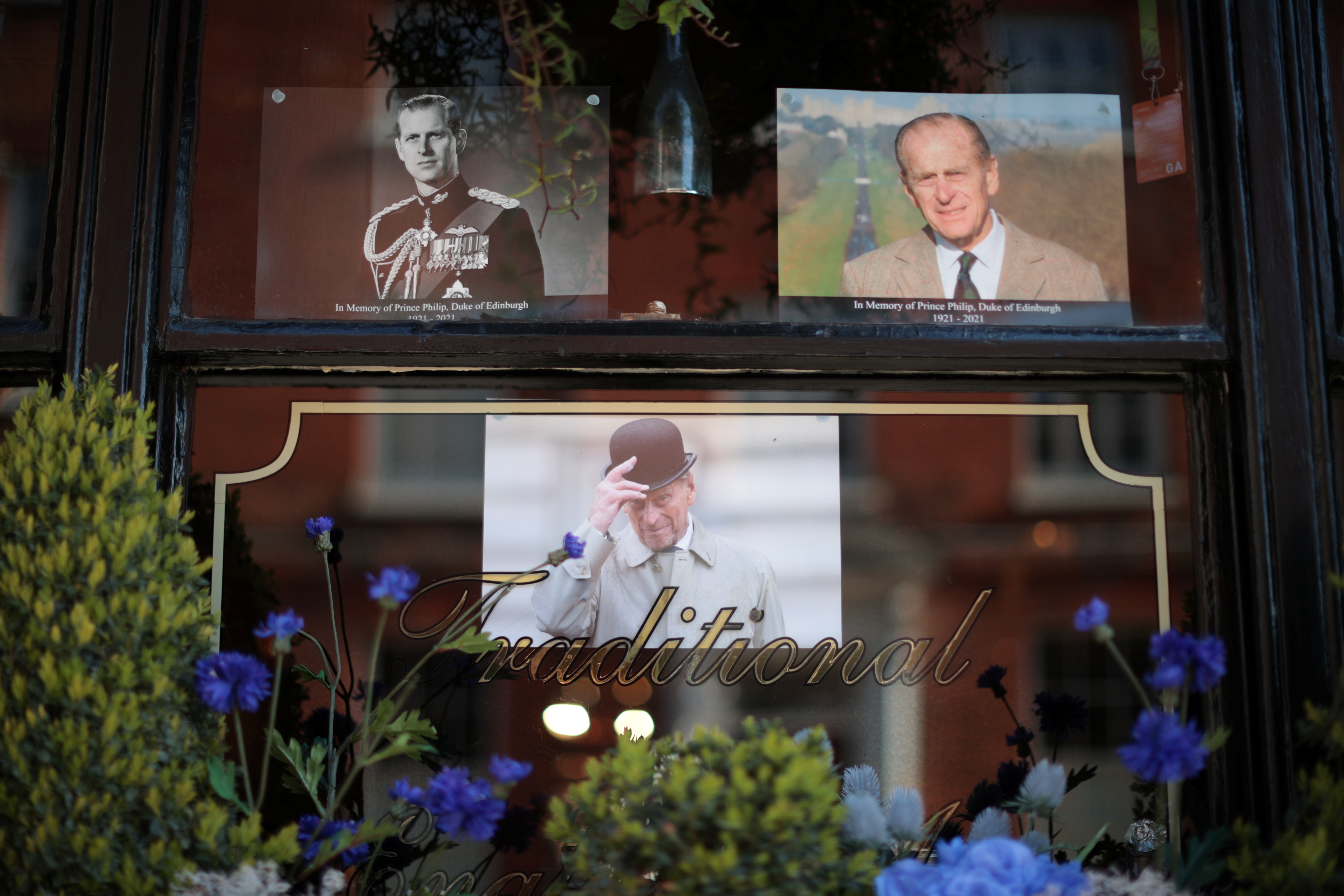 Pictures of Britain's Prince Philip, husband of Queen Elizabeth, are seen at a window in Windsor, near London, Britain, April 15, 2021. REUTERS/Hannah McKay