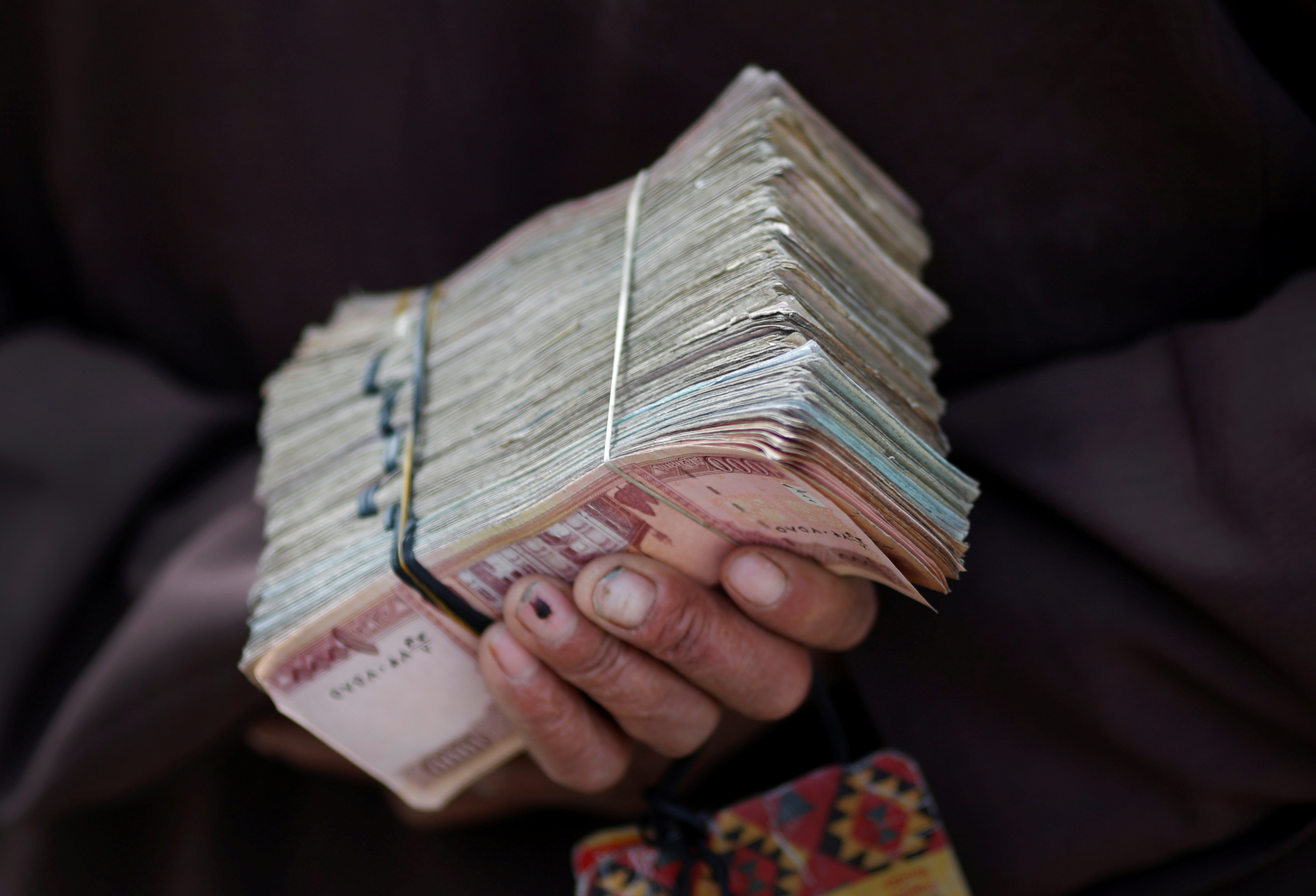 A money changer holds a stack of Afghan currency on a street in central Kabul April 2, 2014. REUTERS/Tim Wimborne