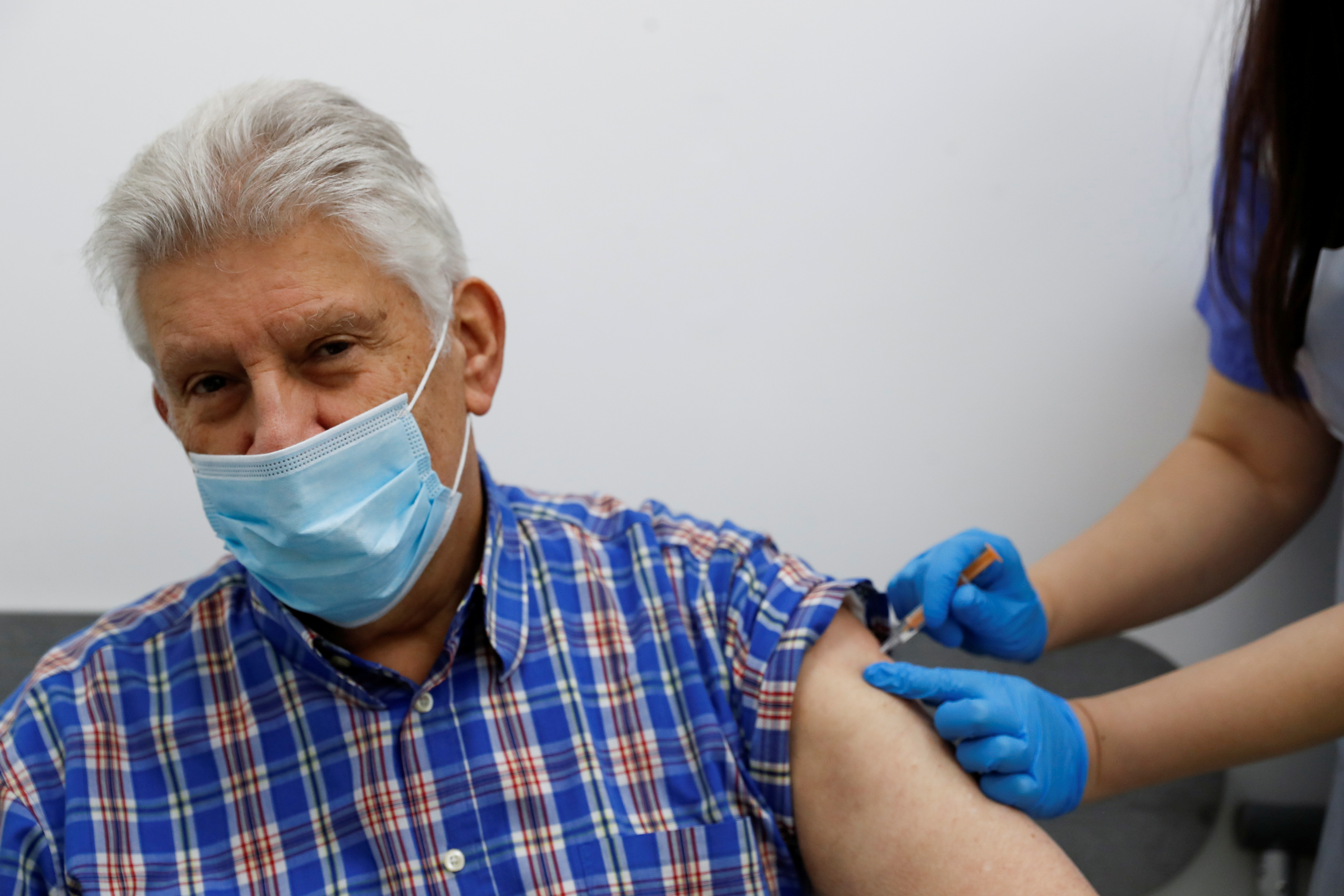 An elderly person receives a dose of the Oxford/AstraZeneca COVID-19 vaccine at Cullimore Chemist, in Edgware, London, Britain January 14, 2021. REUTERS/Paul Childs