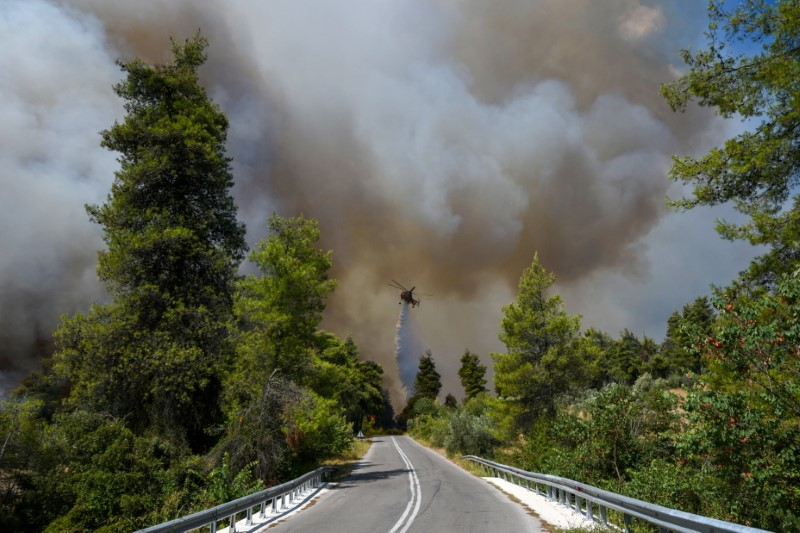 A firefighting helicopter drops a drop of water as a fire breaks out in a forest near the town of Ellinika, on the island of Evia, Greece, on August 8, 2021. REUTERS/Alexandros Avramidis
