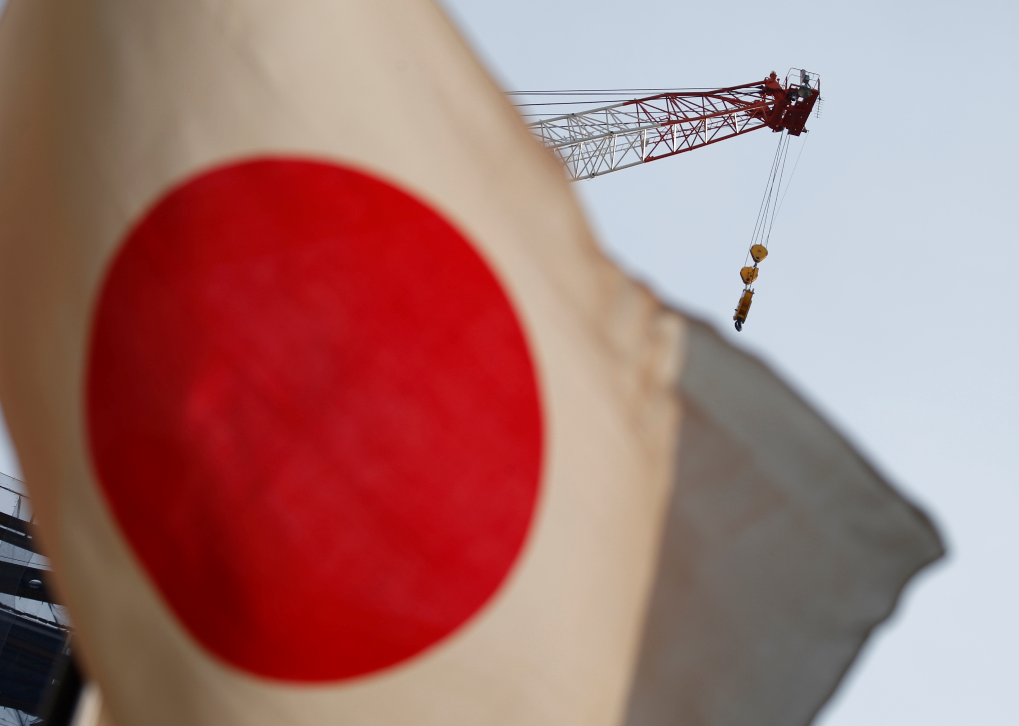 A crane at a construction site is seen behind Japan's national flag in Tokyo, Japan, August 12, 2016. REUTERS/Kim Kyung-Hoon/Files