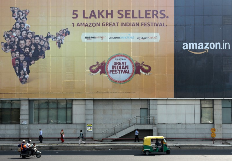 People move past a hoarding of Amazon India outside a metro rail station in New Delhi, India, October 23, 2019. REUTERS/Anushree Fadnavis/File Photo