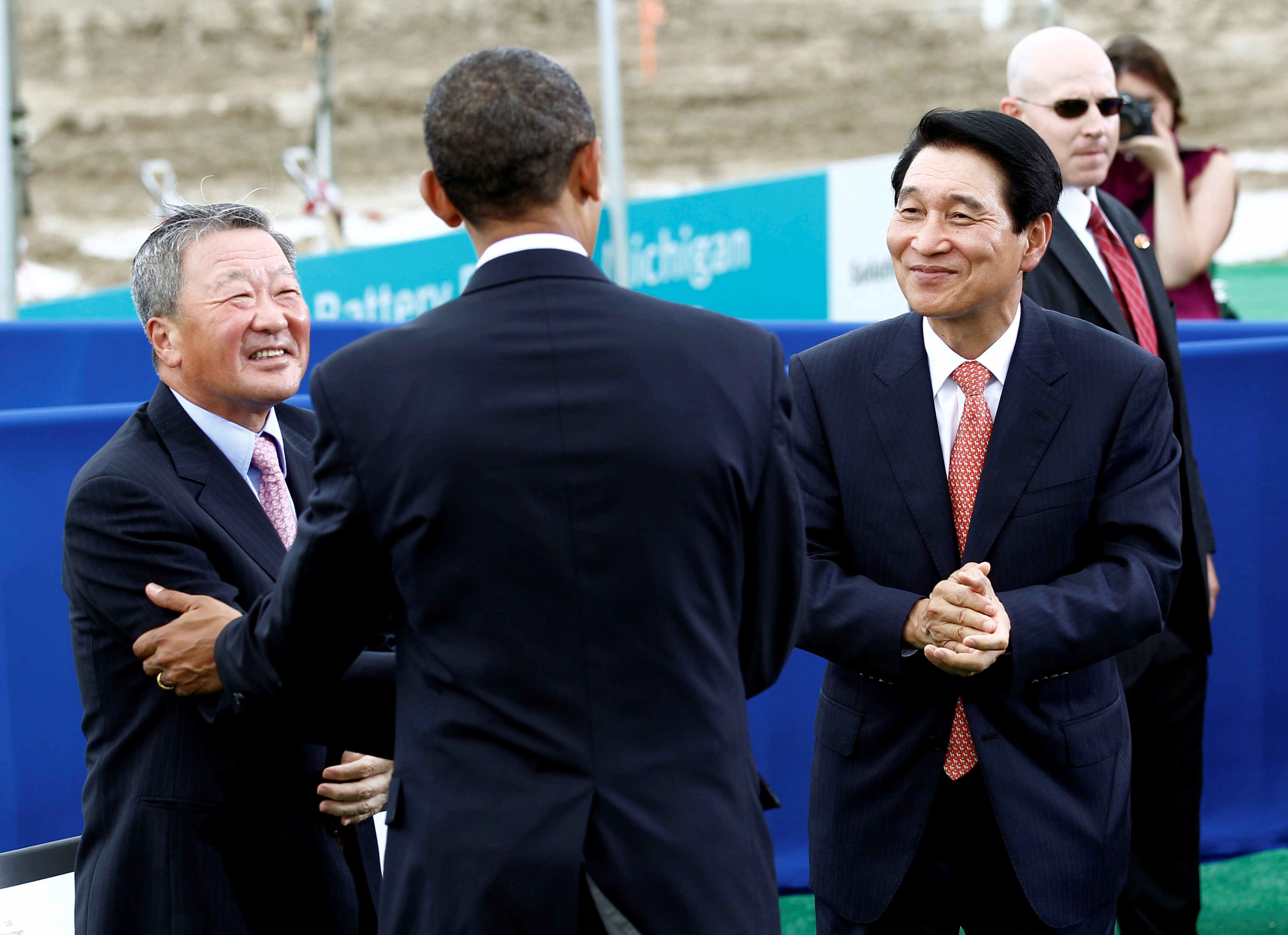 U.S. President Barack Obama greets LG Chem Chairman Bon-Moo Koo (L) and Vice Chairman and CEO of LG Chem Peter Bahn-Suk Kim (R) as he attends the groundbreaking of a factory for Compact Power Inc. in Holland, Michigan July 15, 2010.  REUTERS/Kevin Lamarque/File Photo
