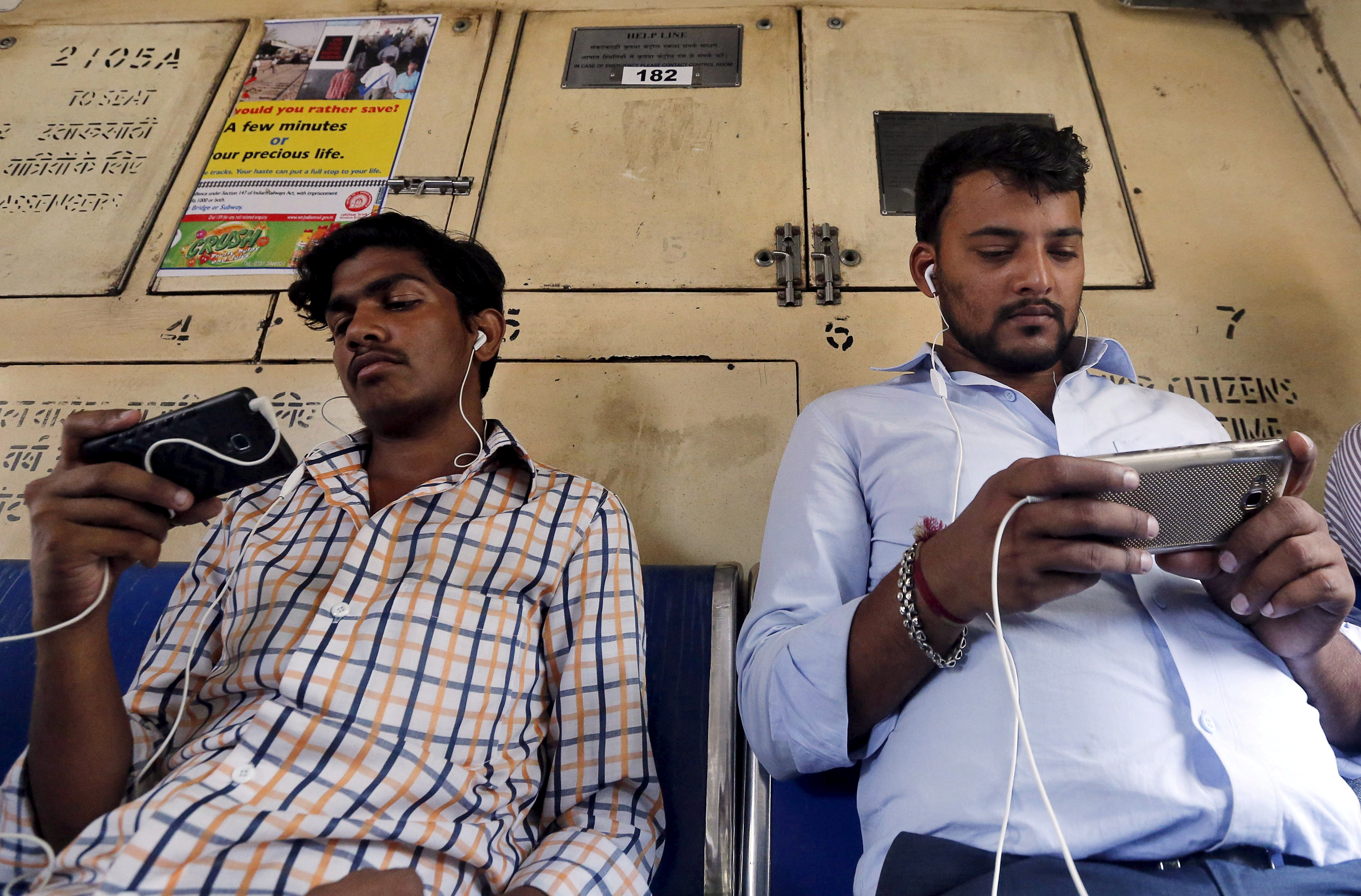 Commuters watch videos on their mobile phones as they travel in a suburban train in Mumbai, India, April 2, 2016.  Picture taken April 2, 2016. REUTERS/Shailesh Andrade/File Photo