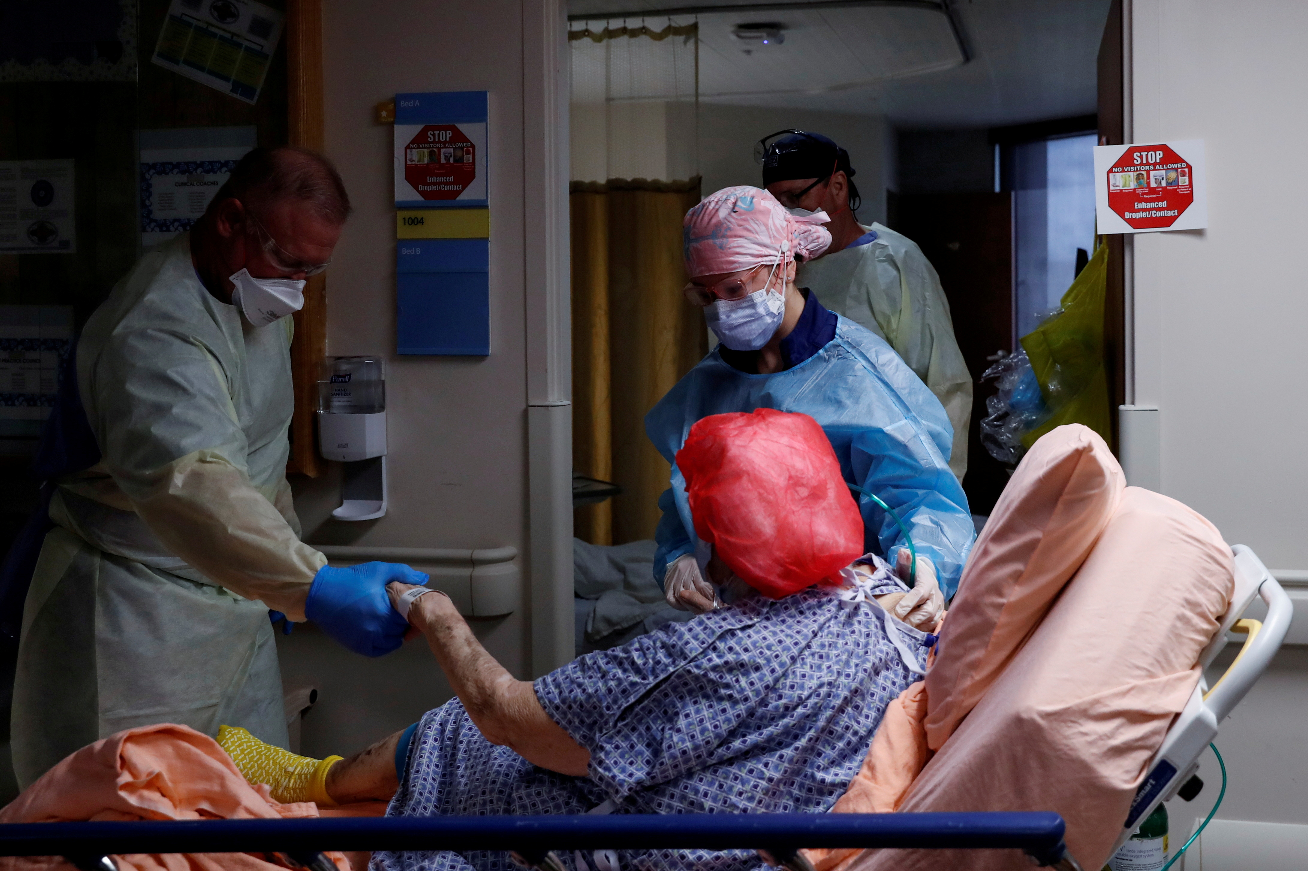 Members of a COVID medical team transport a coronavirus disease (COVID-19) positive patient to their room on the COVID medical unit at Sarasota Memorial Hospital in Sarasota, Florida, U.S., September 21, 2021. REUTERS/Shannon Stapleton/File Photo