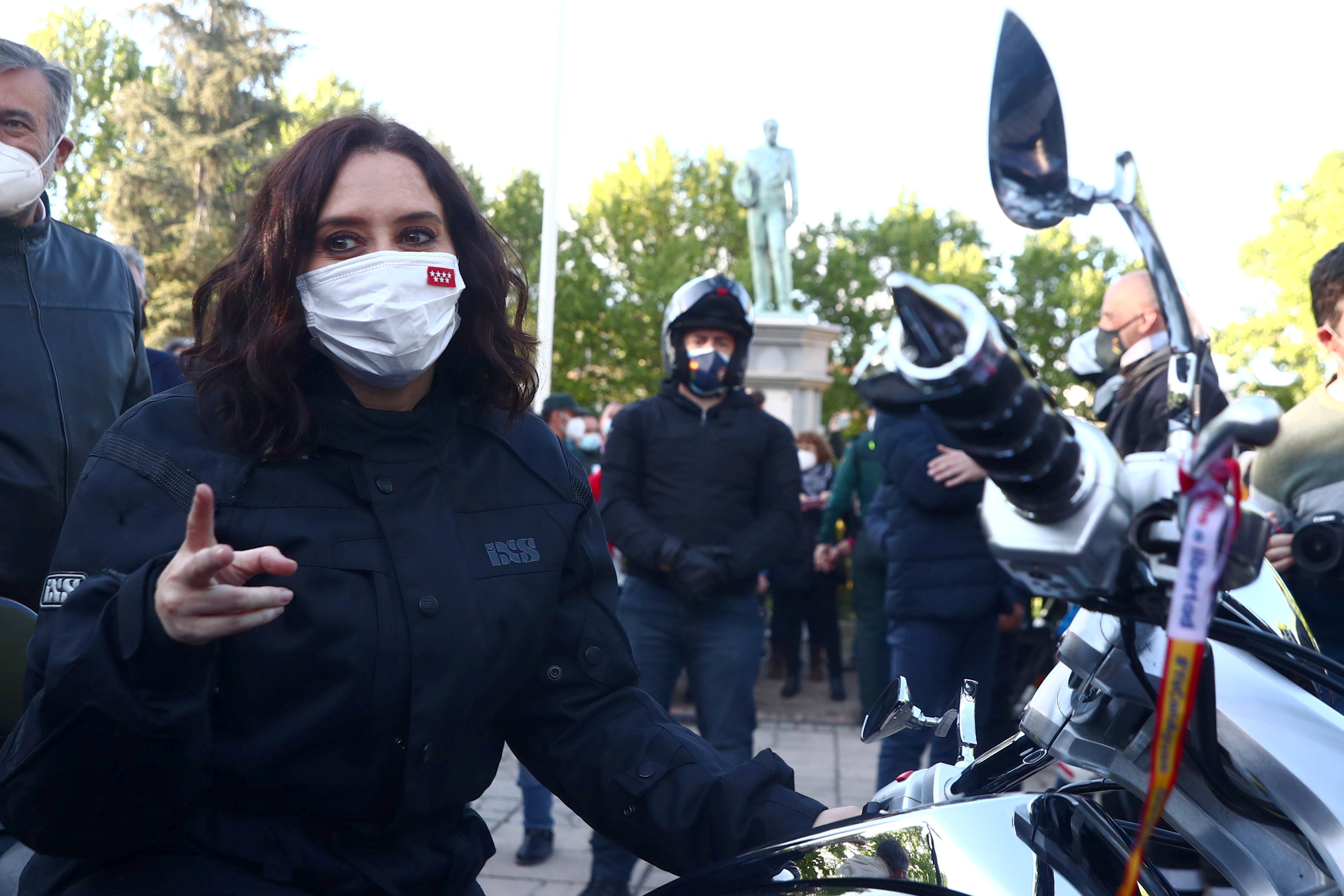 Madrid regional government leader Isabel Diaz Ayuso gestures upon arriving by motorbike to an electoral event ahead upcoming regional elections in Valdemoro, Spain, April 29, 2021. REUTERS/Sergio Perez