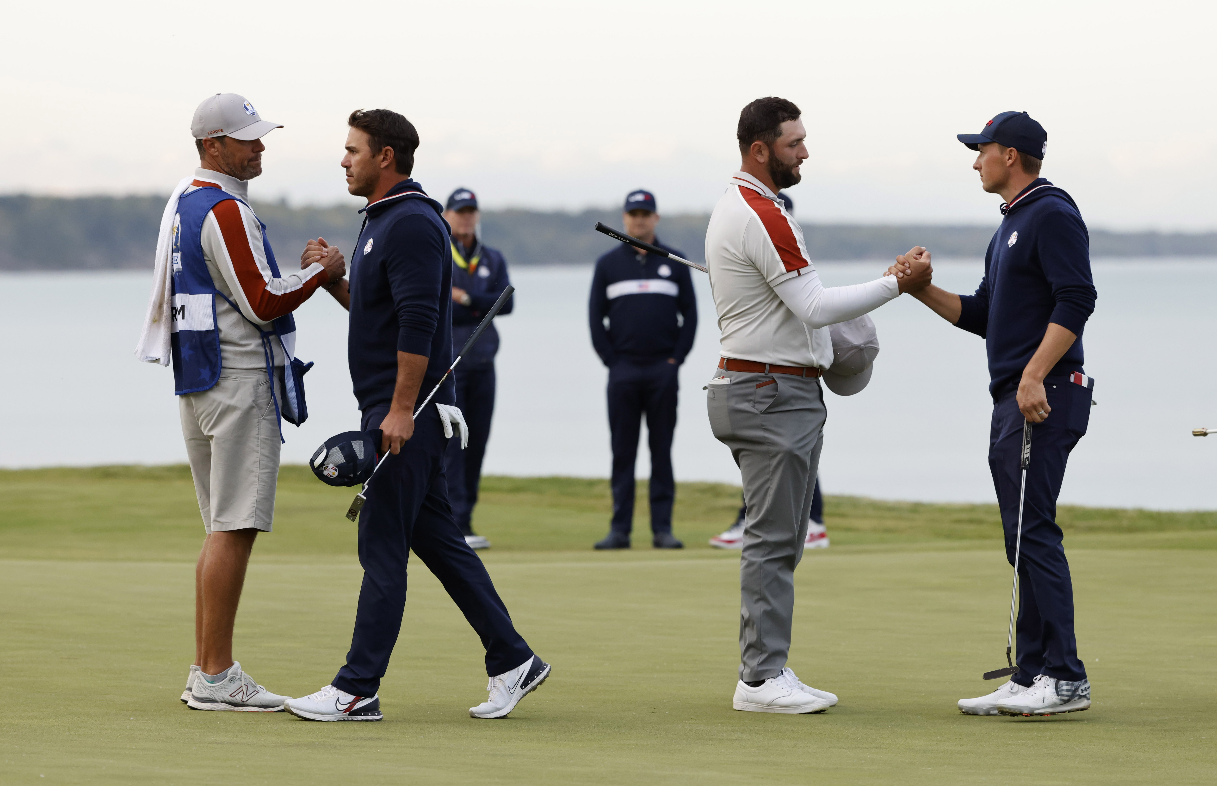 Golf - The 2020 Ryder Cup - Whistling Straits, Sheboygan, Wisconsin, U.S. - September 25, 2021 Team Europe's Jon Rahm shakes hands with Team USA's Jordan Spieth on the 17th green as Team USA's Brooks Koepka looks on after Team Europe win the match during the Four-balls REUTERS/Jonathan Ernst