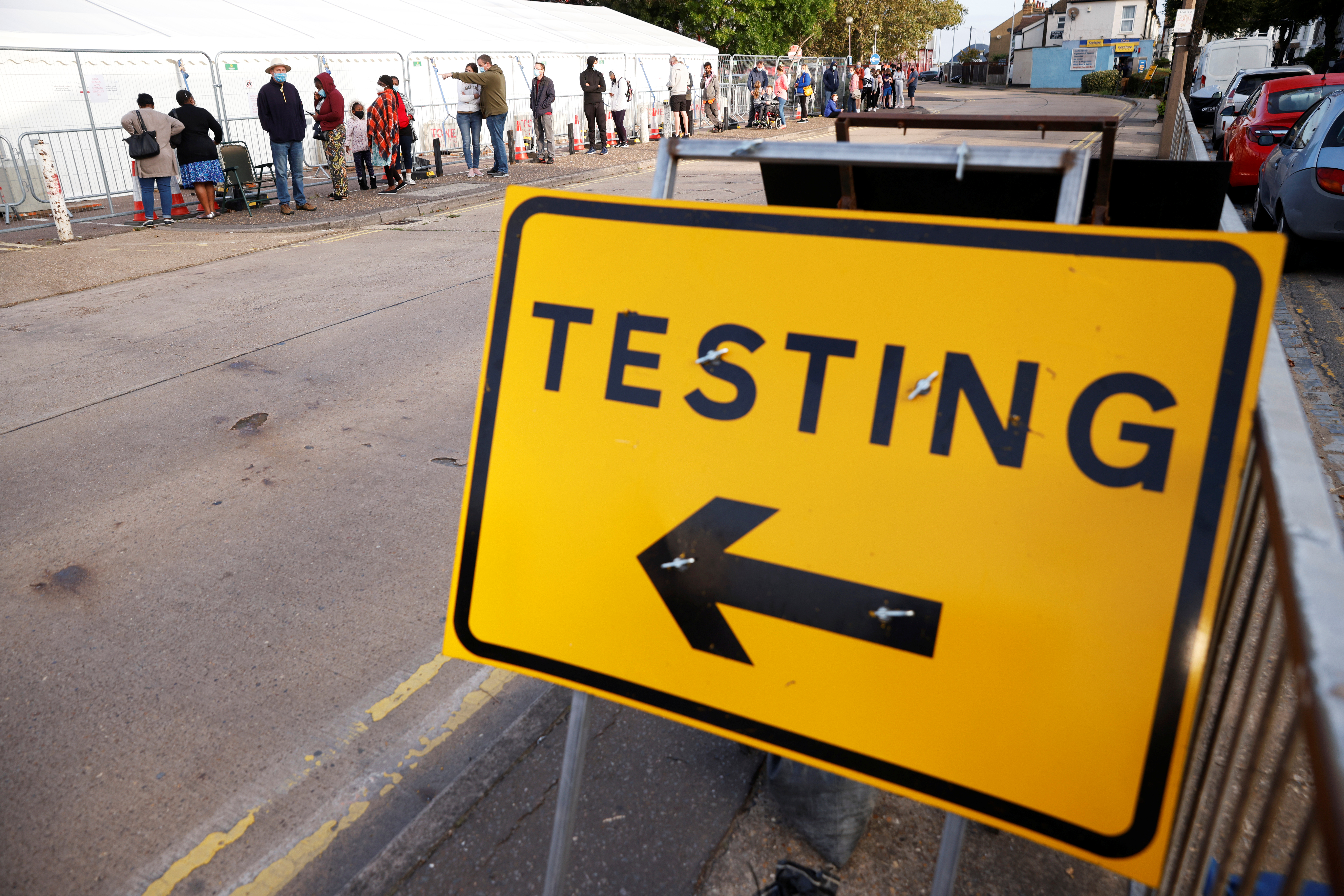 A sign is pictured as people queue outside a test centre, following an outbreak of the coronavirus disease (COVID-19), in Southend-on-sea, Britain September 17, 2020. REUTERS/John Sibley