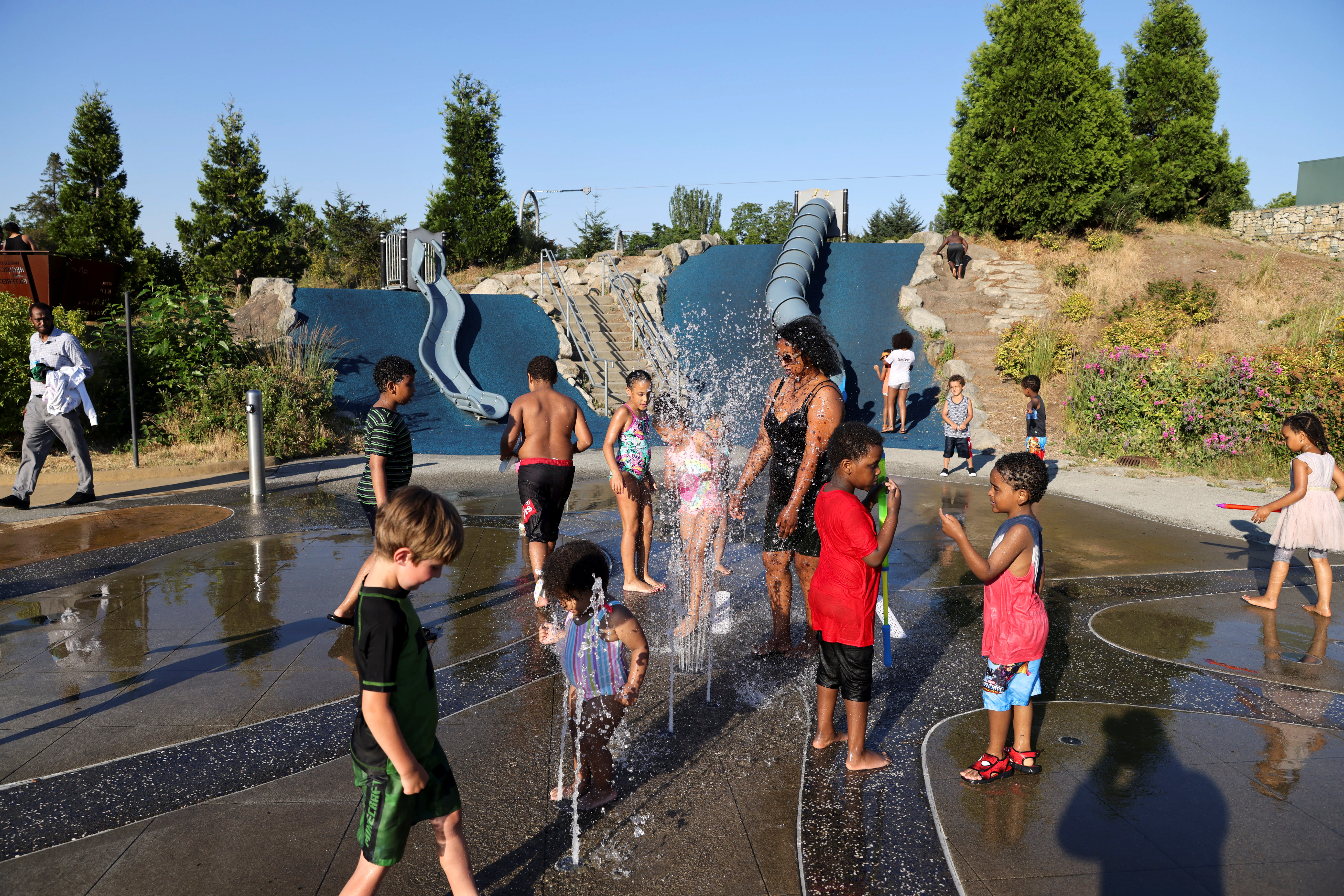 Adults and kids play in a spray park at Jefferson Park during a heat wave in Seattle, Washington, U.S., June 27, 2021. REUTERS/Karen Ducey