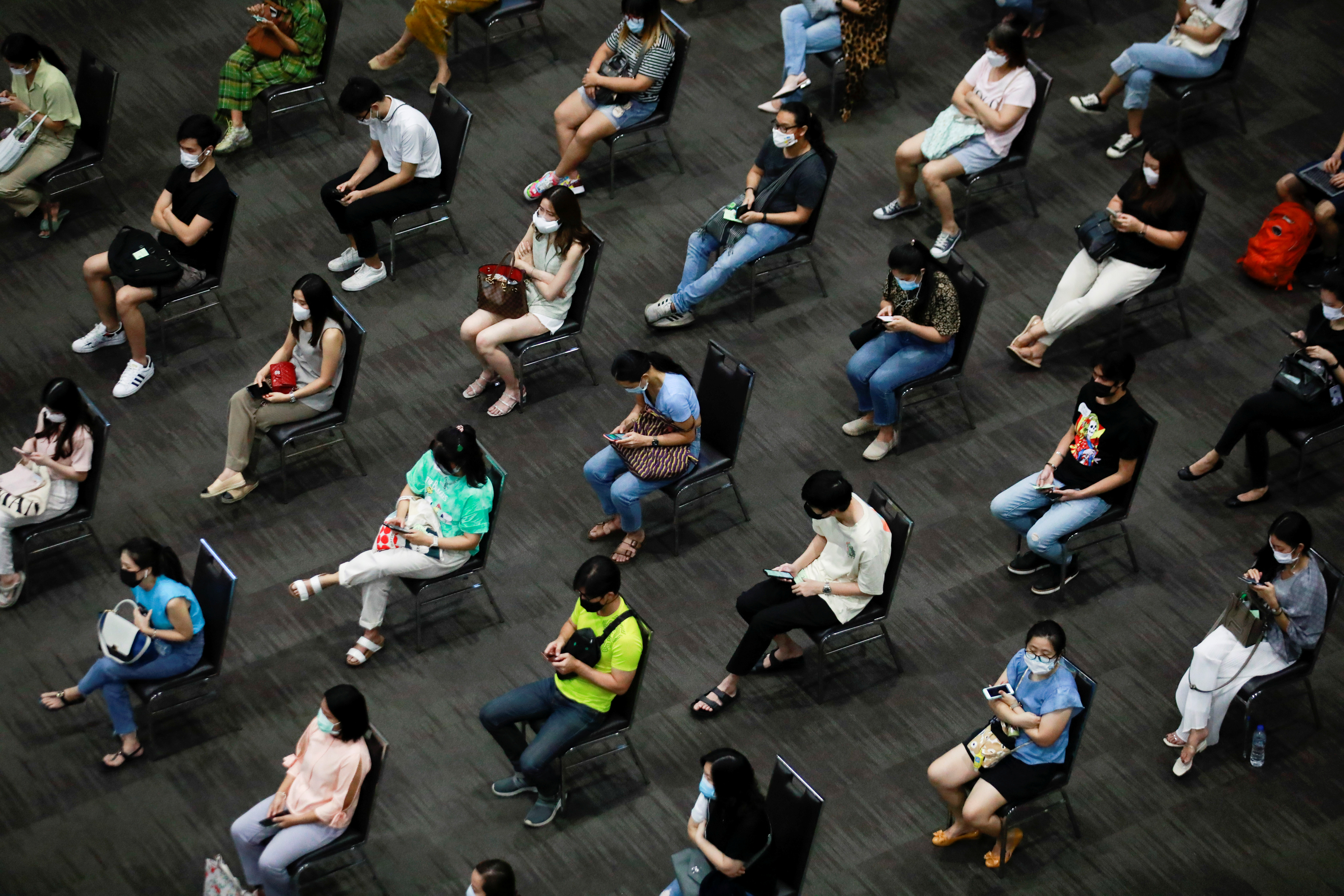 People wait to receive the first dose of the AstraZeneca COVID-19 vaccine against the coronavirus disease (COVID-19) as Thailand start a mass inoculation at a gymnasium inside the Siam paragon Shopping center, Bangkok, Thailand June 7, 2021. REUTERS/Soe Zeya Tun