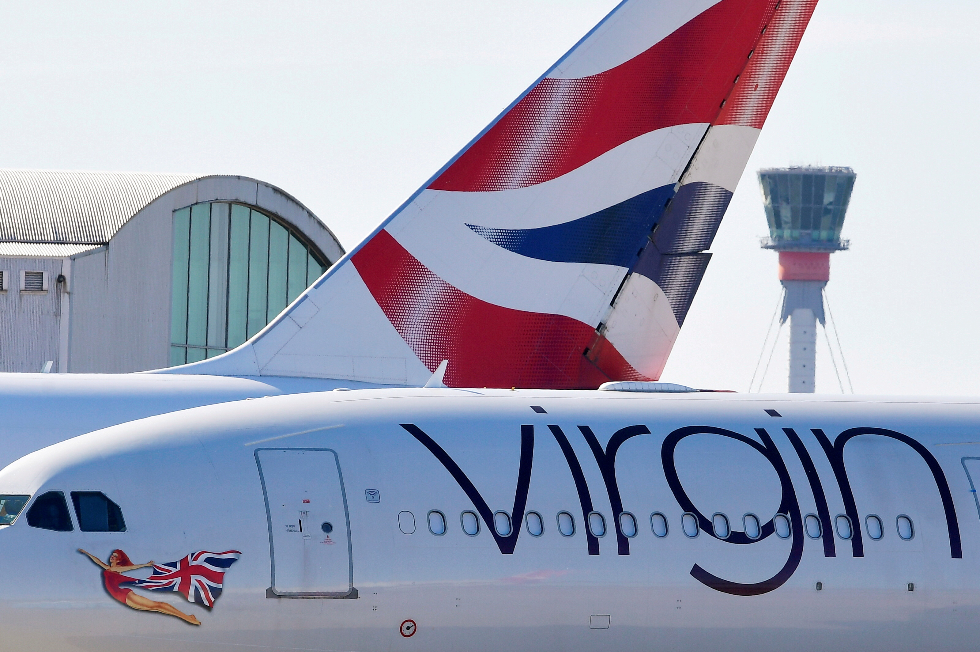 A British airways aeroplane tailfin and a Virgin Atlantic areoplane are seen with the control tower at Heathrow airport., London, Britain, May 5, 2020. REUTERS/Toby Melville