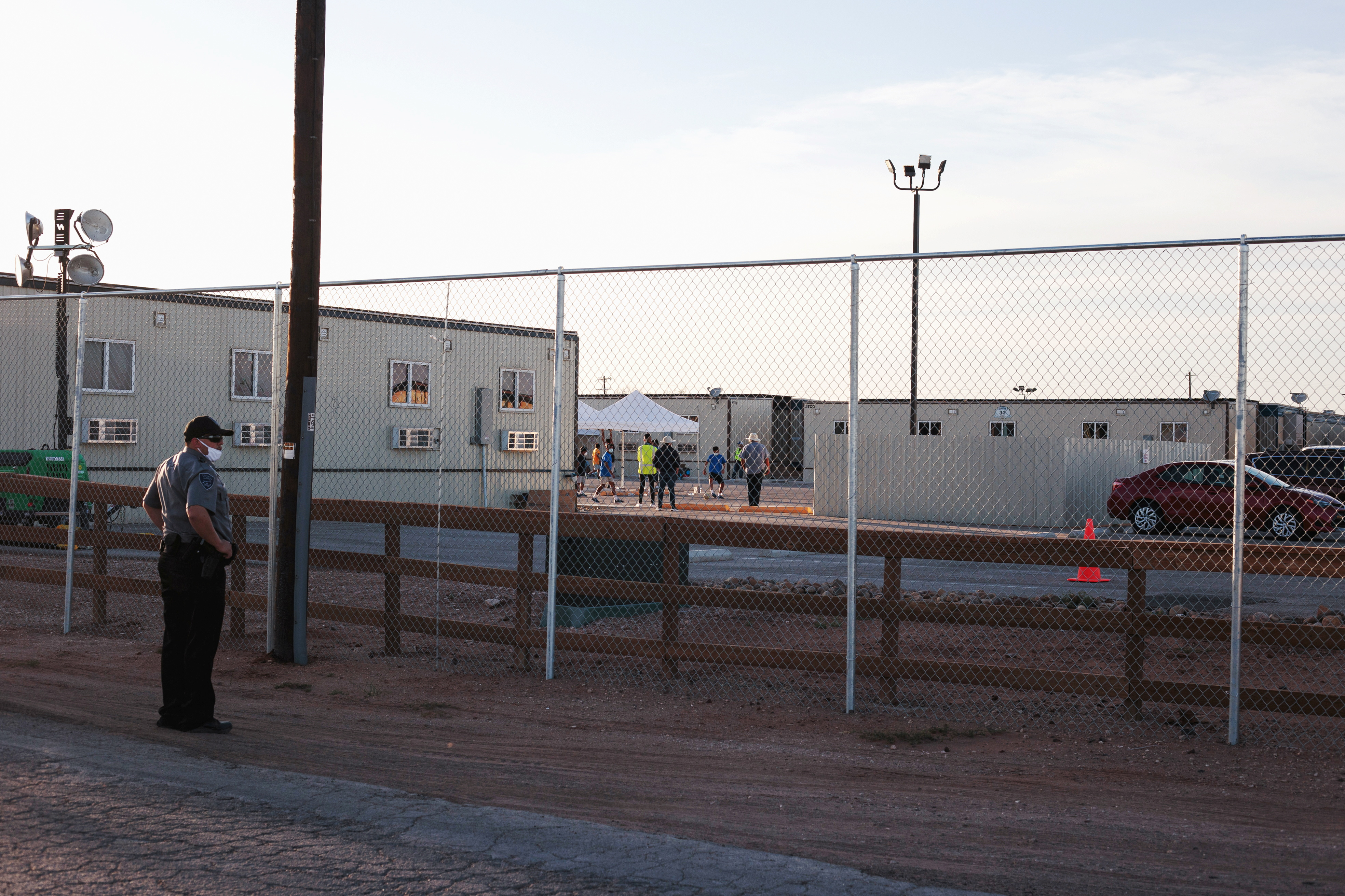 A security guard is seen at the site of a former oil field workers camp which is being used as a temporary housing facility for migrant children in Midland County, Texas, U.S. April 8, 2021.  REUTERS/Paul Ratje