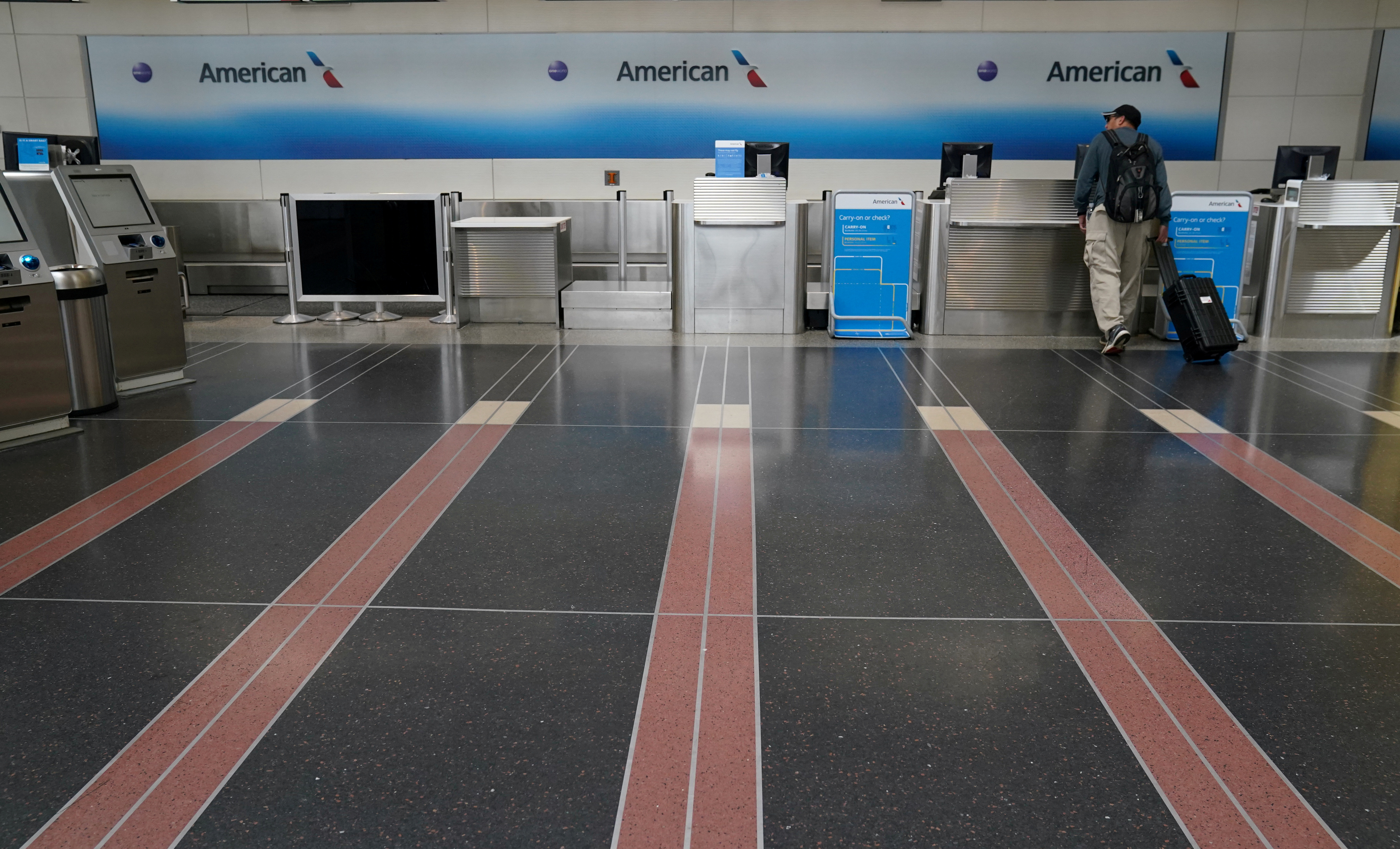 A lone customer seeks assistance at an American Airlines check-in counter at Washington