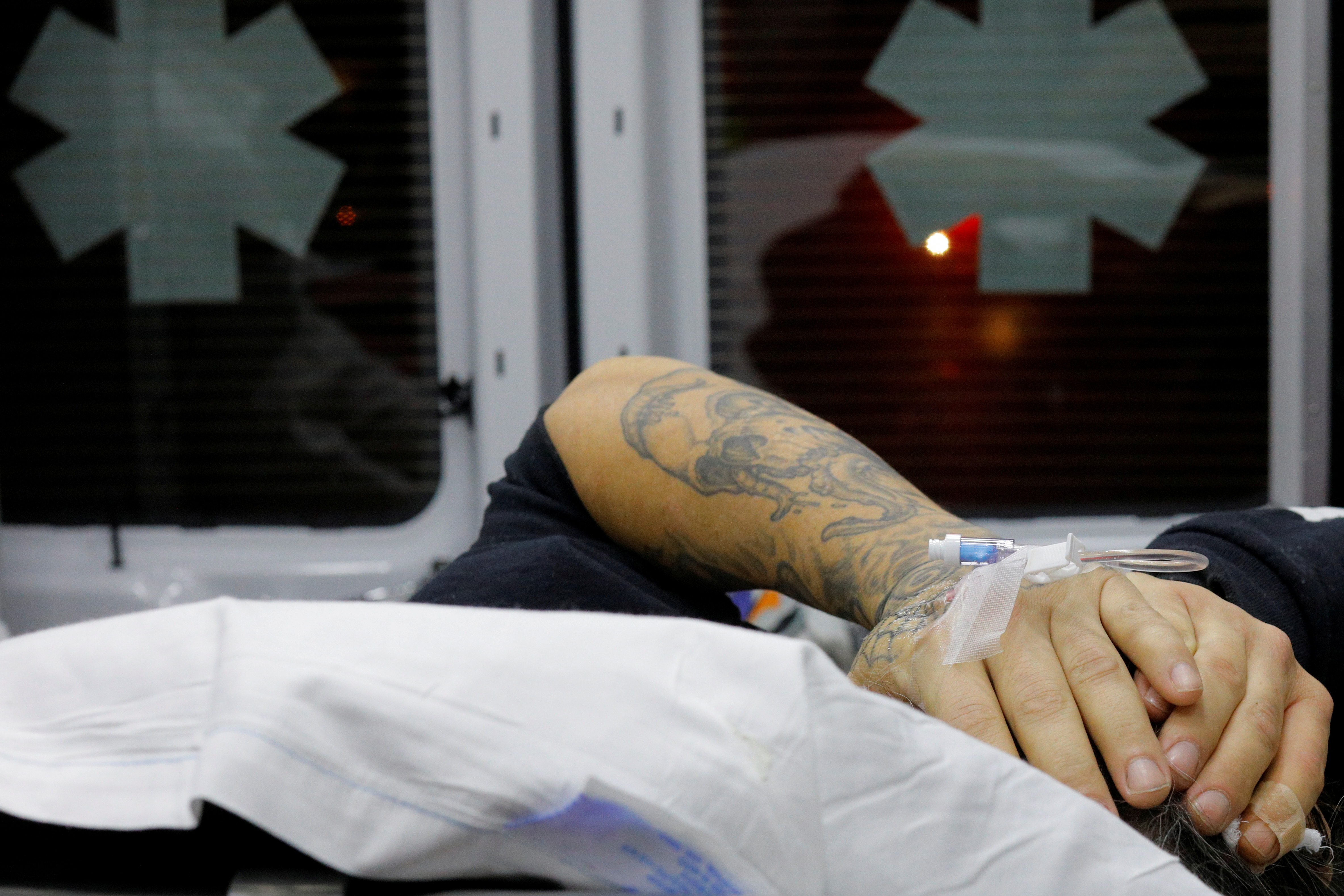 A 41-year-old man found unconscious after overdosing on opioids in the driver's seat of a car, with the engine running and the transmission in drive, puts his hands over his head in the back of a Cataldo Ambulance at a gas station in the Boston suburb of Malden, Massachusetts, December 2, 2017.  REUTERS/Brian Snyder/File Photo