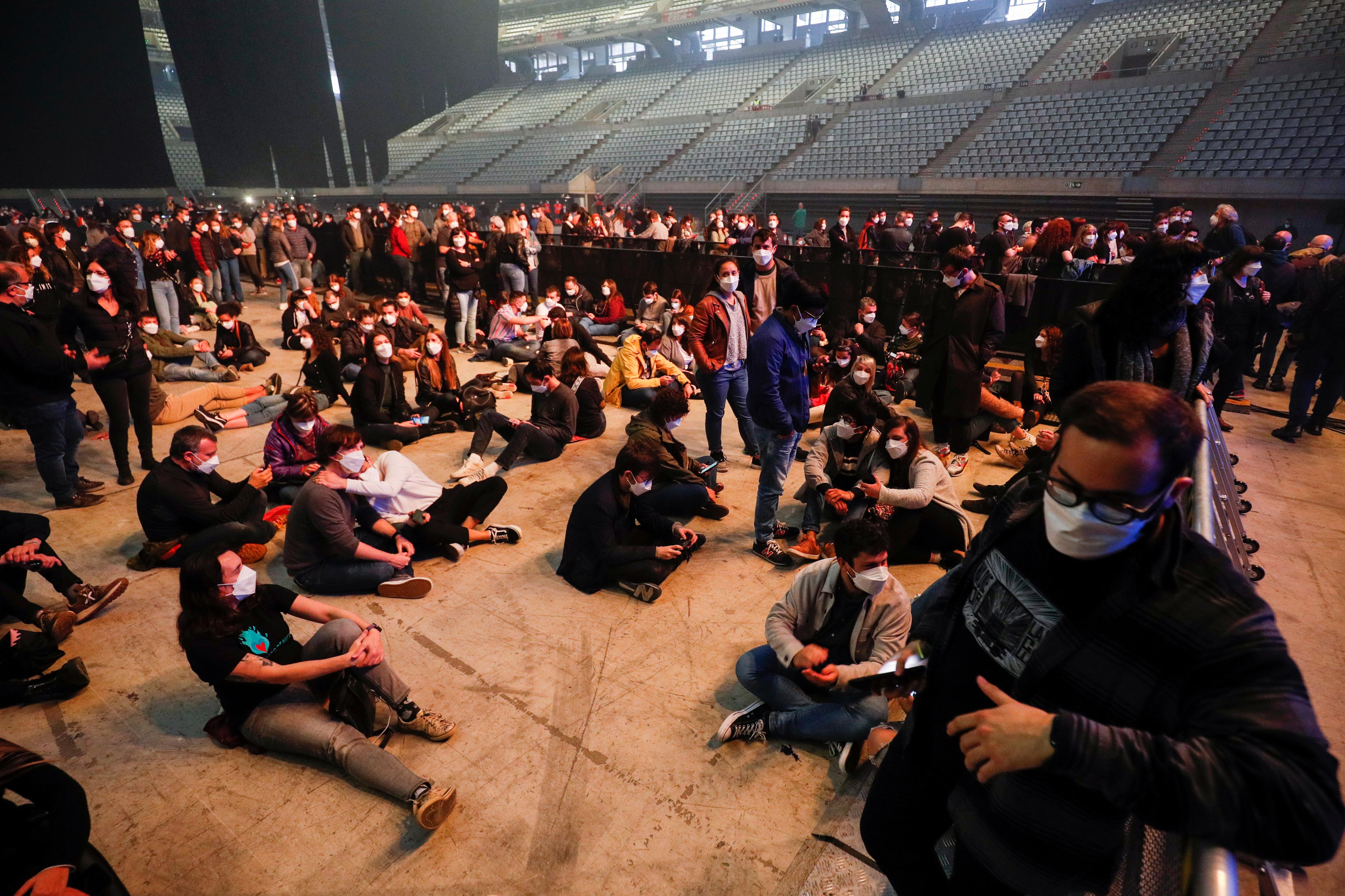 Spectators wearing face masks wait before a concert of