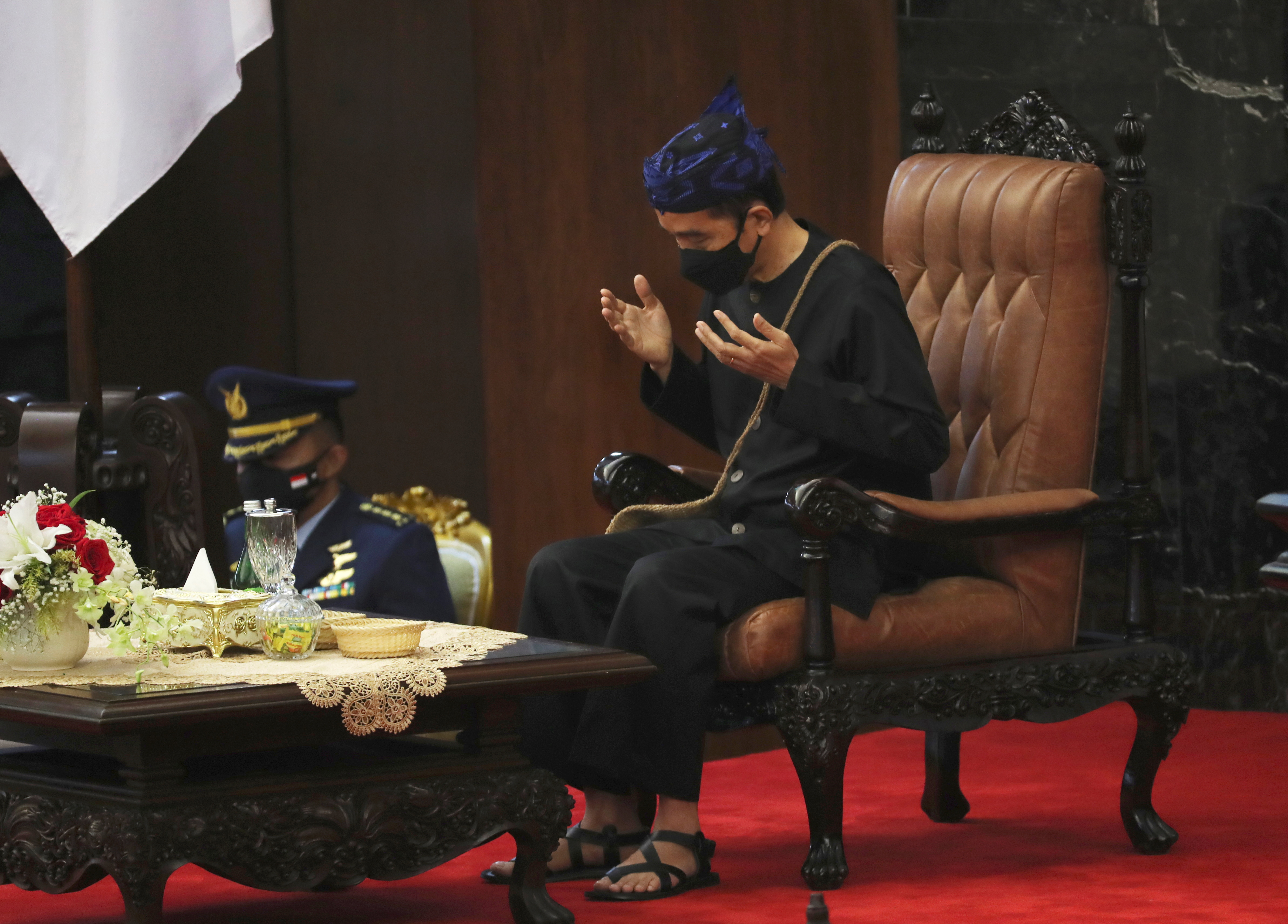 Indonesian President Joko Widodo, wearing a traditional Baduy outfit, prays after delivering his State of the annual Nation Address ahead of the country's Independence Day, at the parliament building in Jakarta, Indonesia, August 16, 2021. Achmad Ibrahim/Pool via REUTERS