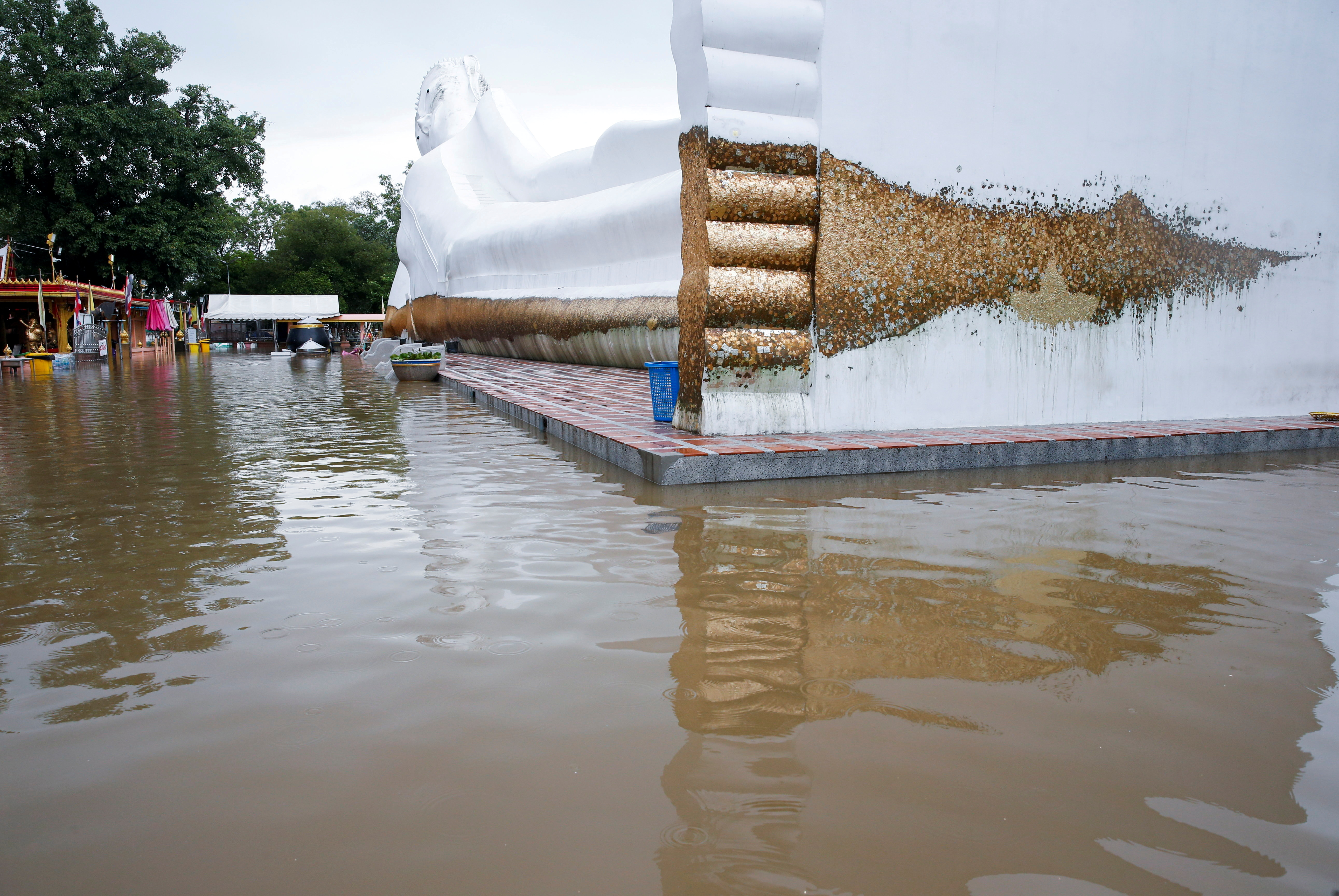 A lying Buddha statue is seen surrounded by floodwaters at a temple in Ayutthaya, Thailand, October 6, 2021. REUTERS/Soe Zeya Tun