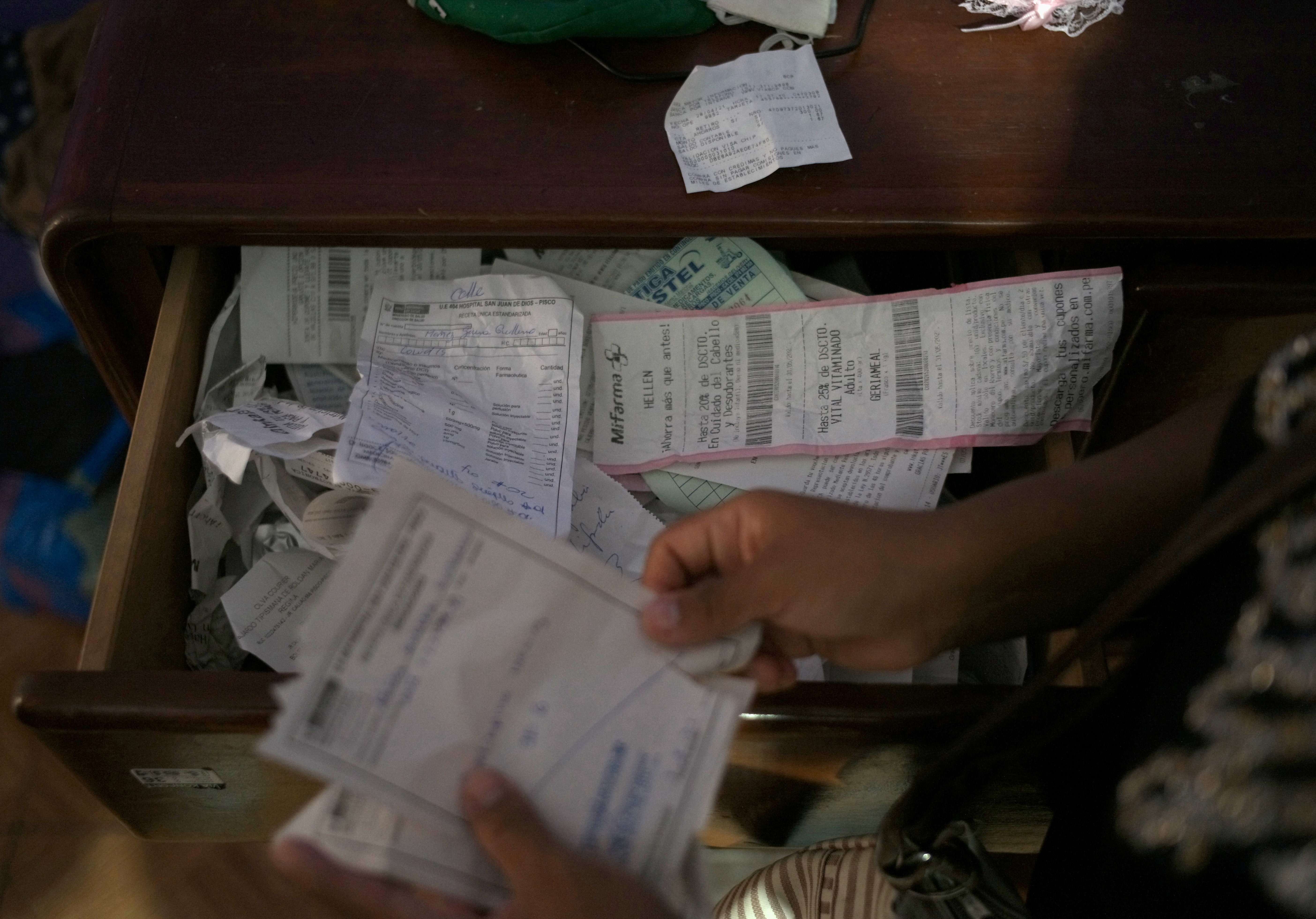 Hellen Nanez, who lost 13 relatives to the coronavirus disease (COVID-19) and whose father is being treated for COVID-19 in the Intensive Care Unit, reviews medical bills and receipts at her home in Pisco, Peru, May 8, 2021. Picture taken May 8, 2021. REUTERS/Alessandro Cinque - RC2NBN9TY7GR