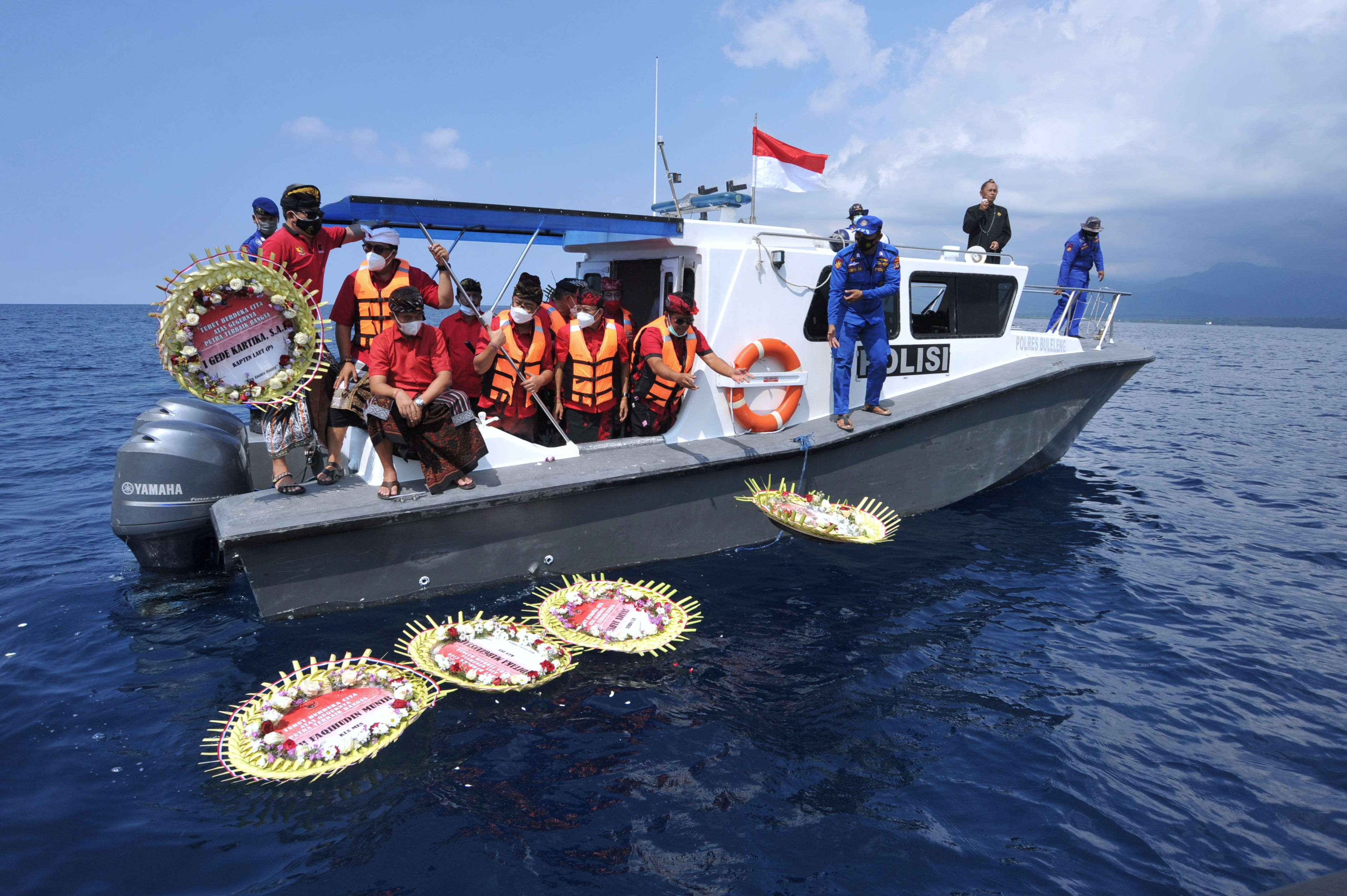 People throw flowers and petals with names of the sunken KRI Nanggala-402 submarine crew members from the boat during a prayer at the sea near Labuhan Lalang, Bali, Indonesia April 26, 2021, in this photo taken by Antara Foto/Fikri Yusuf/via Reuters.