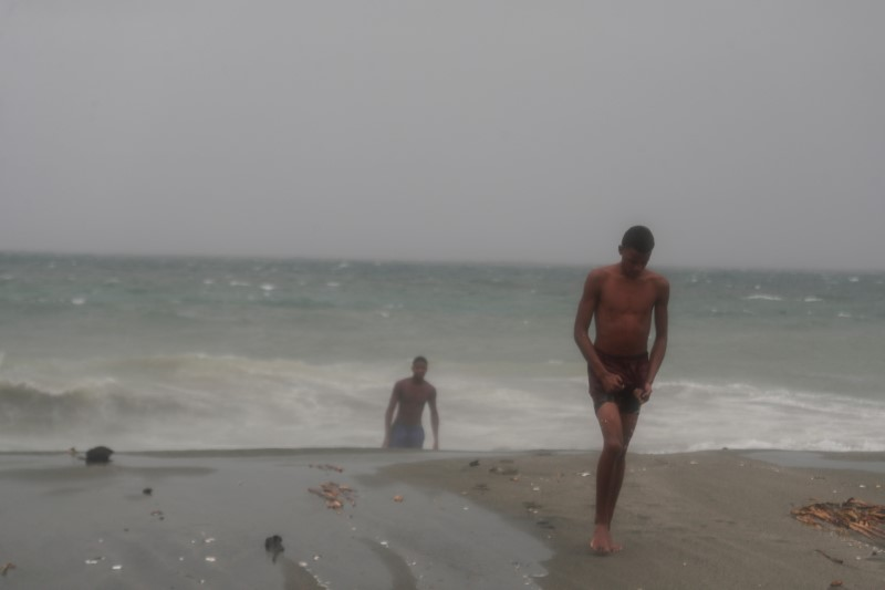 Men walk off a beach during the passage of Tropical Storm Fred in Santo Domingo, Dominican Republic August 11, 2021. REUTERS/Ricardo Rojas
