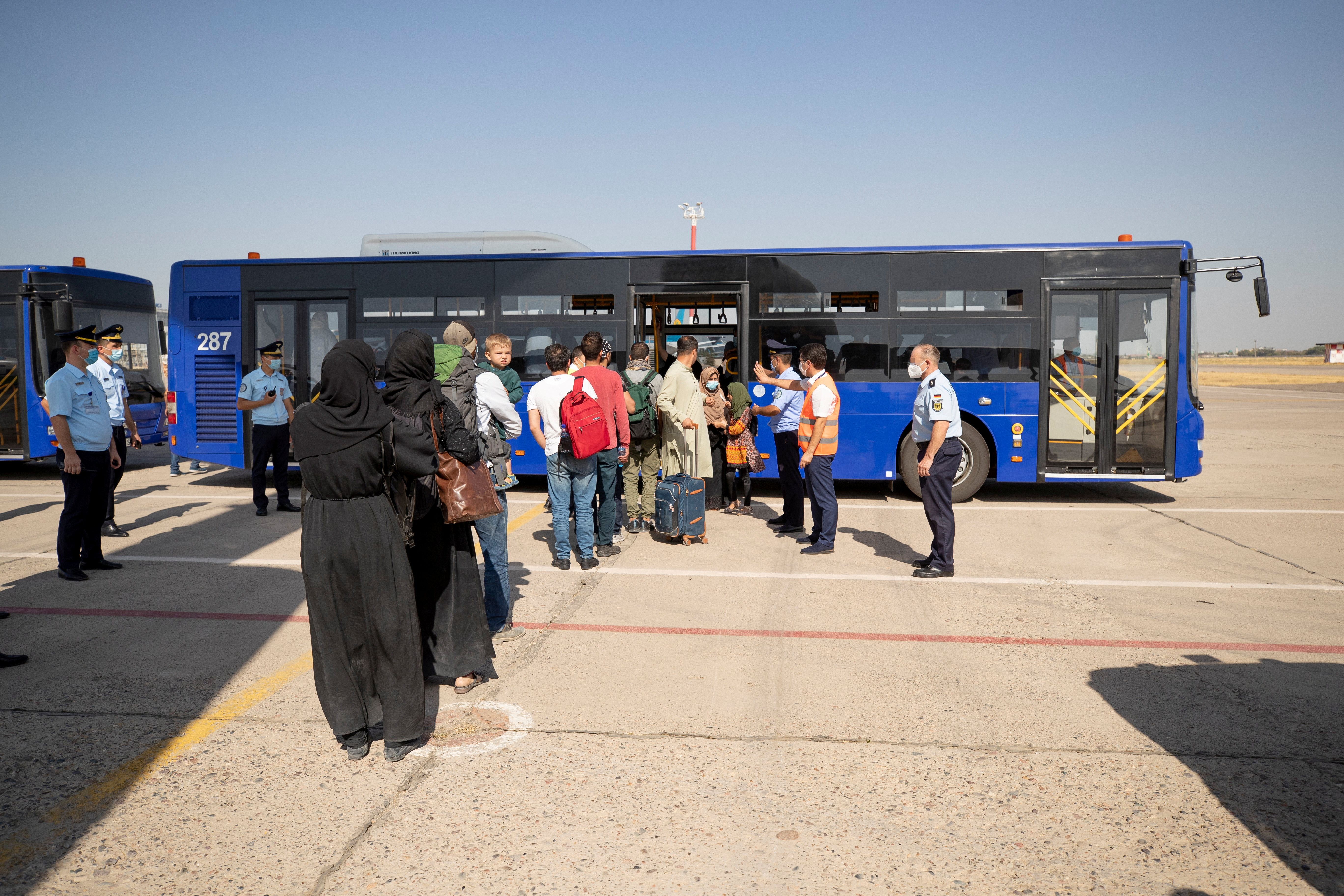 A handout photo obtained from the Bundeswehr Twitter account @Bw_Einsatz on August 18, 2021 shows evacuees from Afghanistan as they board a bus after their arrival in an Airbus A400 transport aircraft of the German Air Force Luftwaffe in Tashkent, Uzbekistan. Marc Tessensohn/Twitter @Bw_Einsatz/Handout via REUTERS    ATTENTION EDITORS - THIS IMAGE HAS BEEN SUPPLIED BY A THIRD PARTY.   NO RESALES. NO ARCHIVES   PARTS OF THE IMAGE HAVE BEEN PIXELATED AT SOURCE.