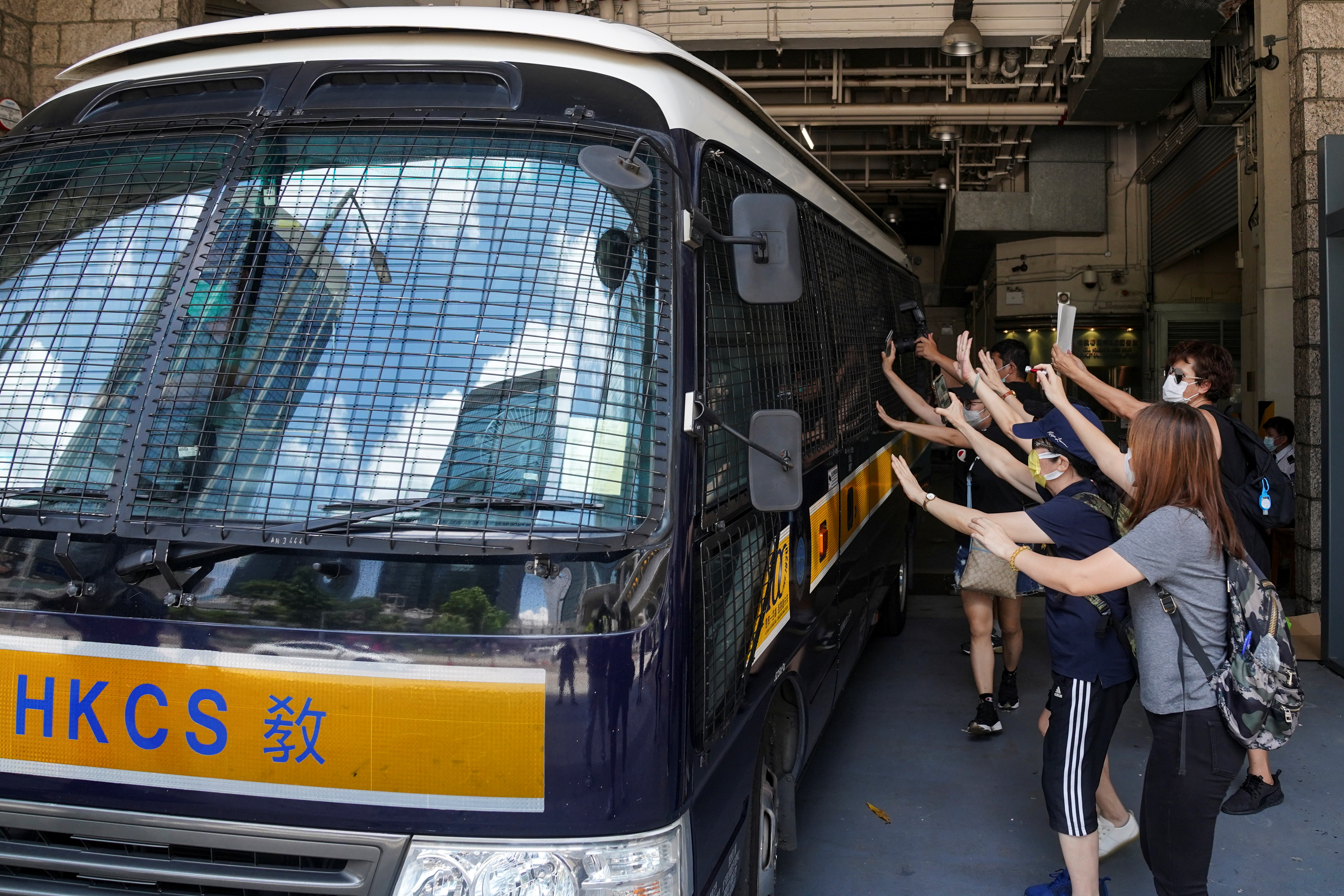Supporters bid farewell to a prison van transporting Tong Ying-kit, a Hong Kong resident charged under the city's new national security law, who has been denied bail again in Hong Kong, China, August 25, 2020. REUTERS/Lam Yik