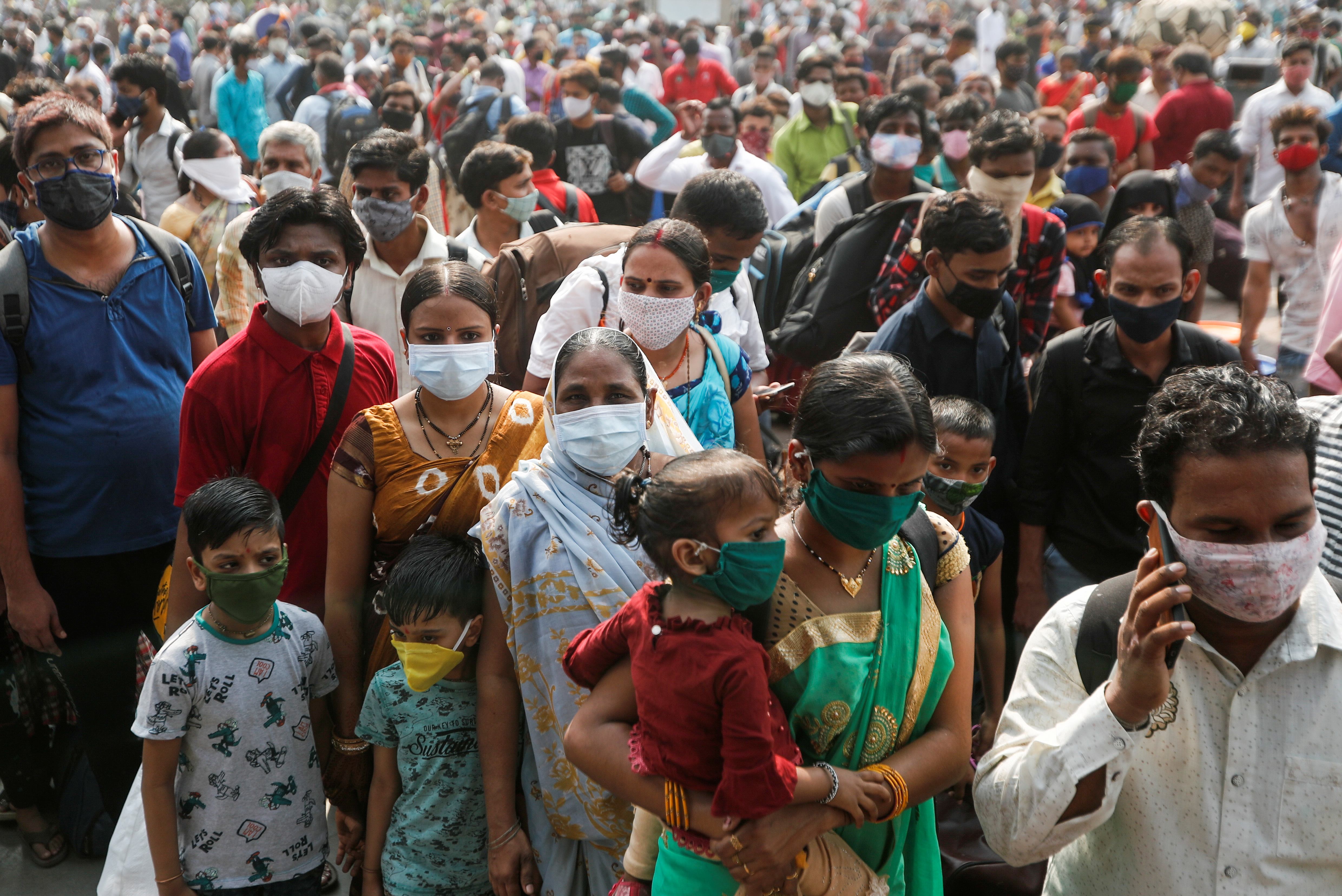 People wearing protective masks stand outside a railway station amidst the spread of the coronavirus disease (COVID-19), in Mumbai, India, April 13, 2021. REUTERS/Francis Mascarenhas