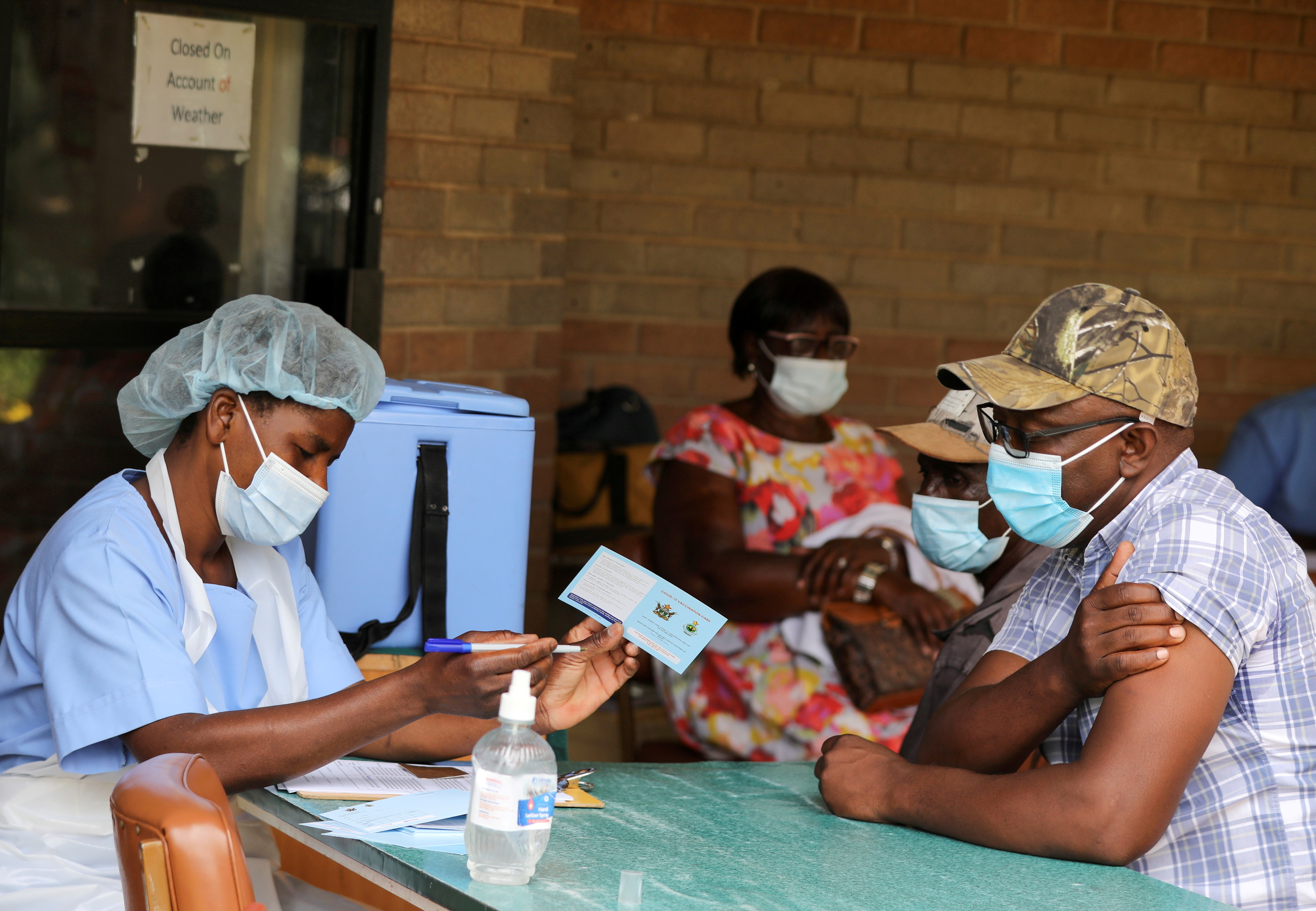 A man receives a certificate after being vaccinated against the coronavirus disease (COVID-19) at Wilkins Hospital in Harare, Zimbabwe, March 24, 2021. REUTERS/Philimon Bulawayo/File Photo
