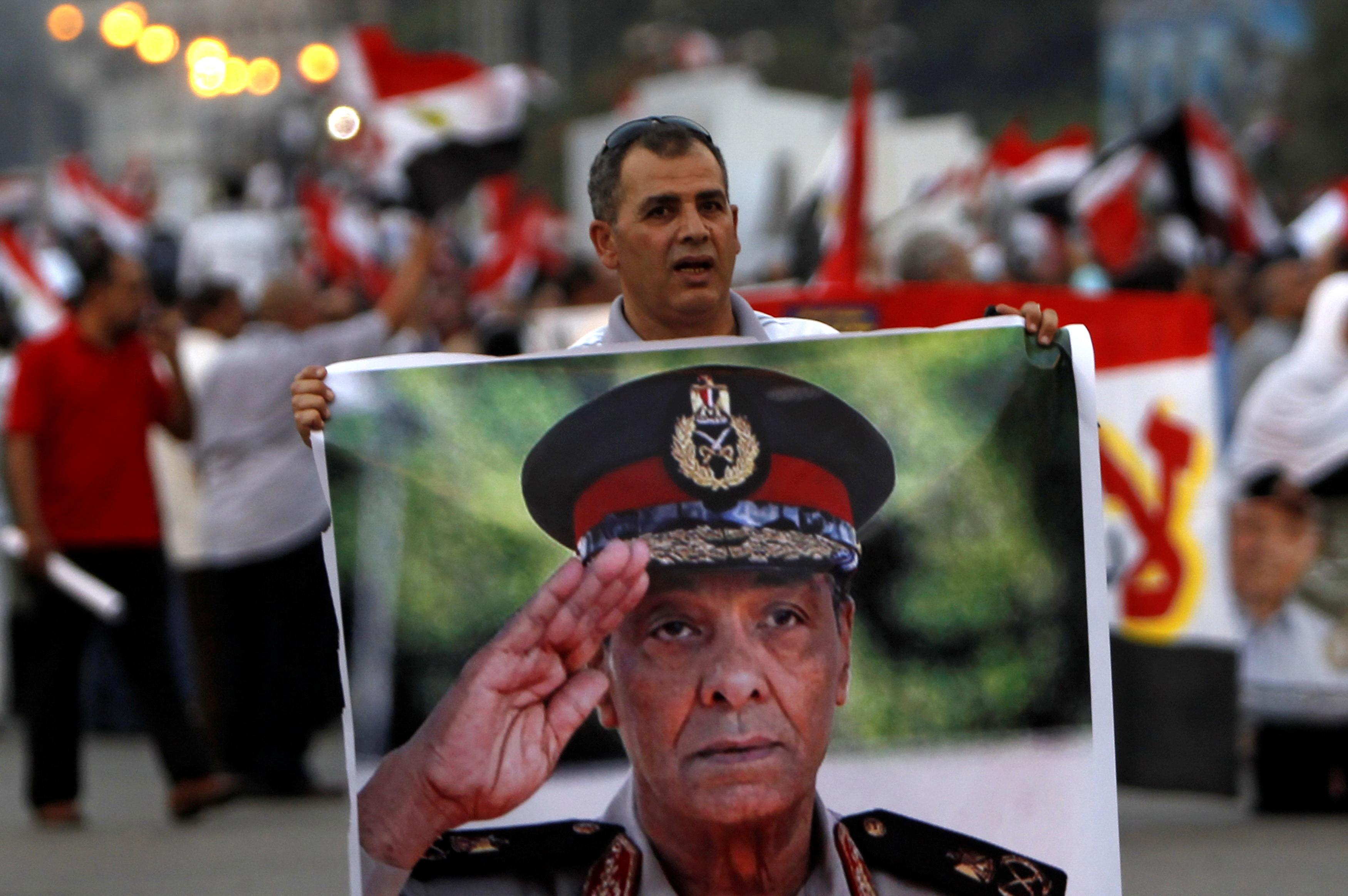 A supporter of former prime minister and presidential candidate Ahmed Shafik holds a poster of Field Marshal Mohamed Hussein Tantawi, the head of the ruling Supreme Council of the Armed Forces (SCAF) during a rally in front of the military parade stand at Nasr City in Cairo June 23, 2012. REUTERS/Amr Abdallah Dalsh/File Photo
