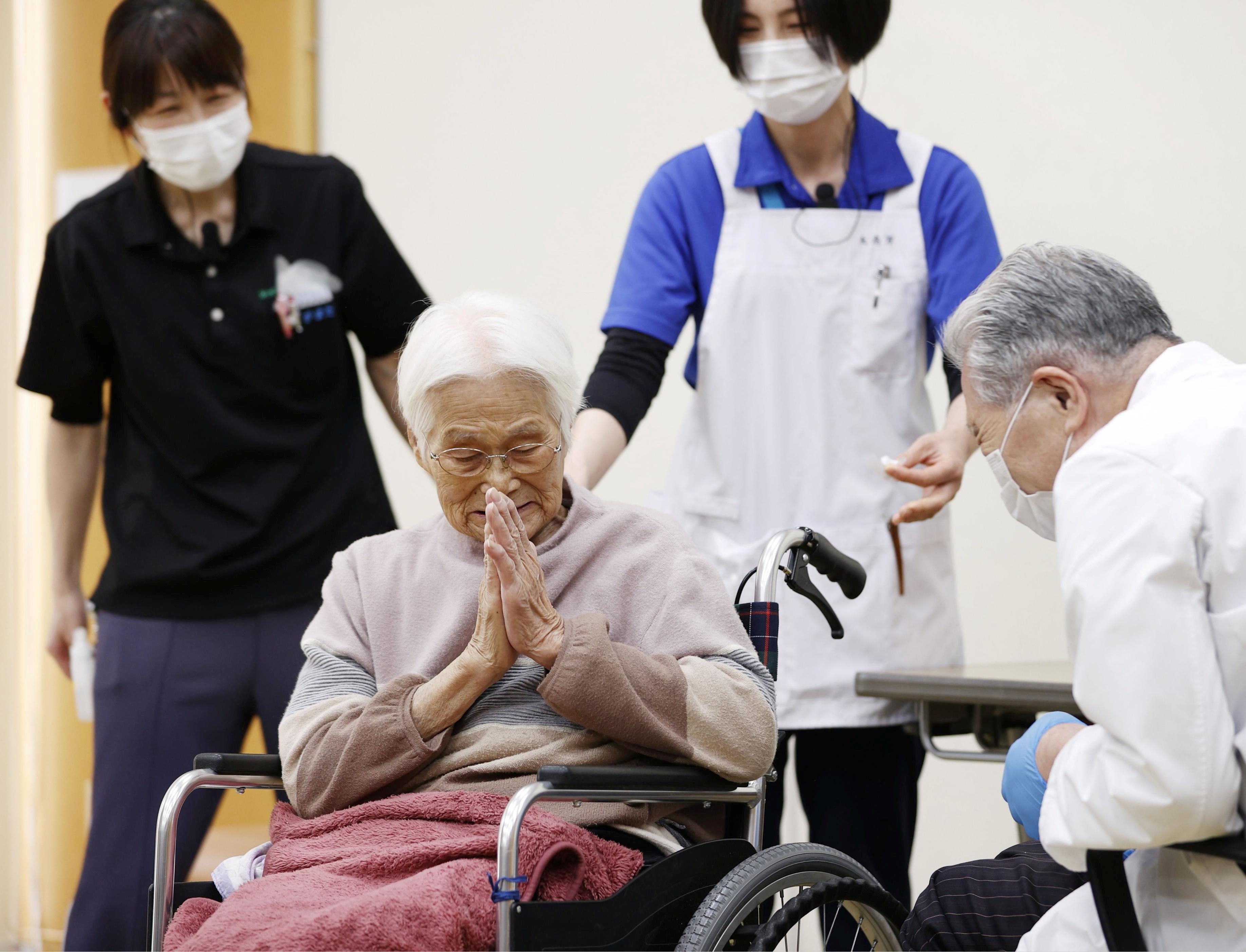 An elderly woman gestures to express gratitude after receiving a coronavirus disease (COVID-19) vaccination in Itami, western Japan April 12, 2021, in this photo released by Kyodo. Kyodo/via REUTERS