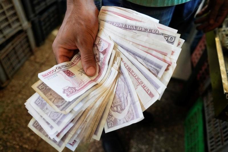 A vendor shows Cuban pesos notes in a public market in Havana, Cuba, June 12, 2021. Picture taken on June 12, 2021. REUTERS/Alexandre Meneghini