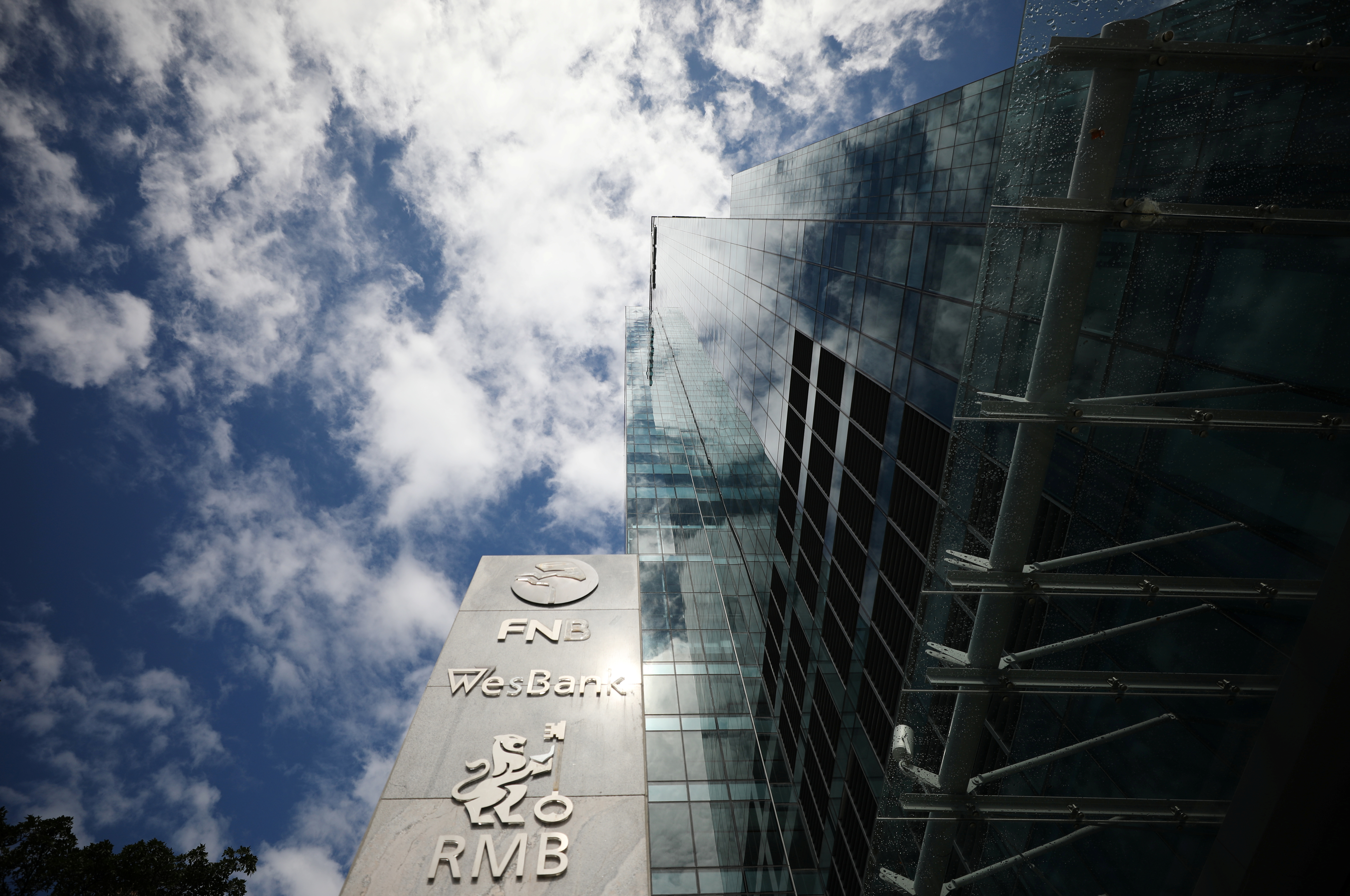 The logos of companies Rand Merchant Bank, FNB, and Wesbank are seen outside the FirstRand offices in Cape Town, South Africa, March 11, 2019. Picture taken March 11, 2019. REUTERS/Mike Hutchings