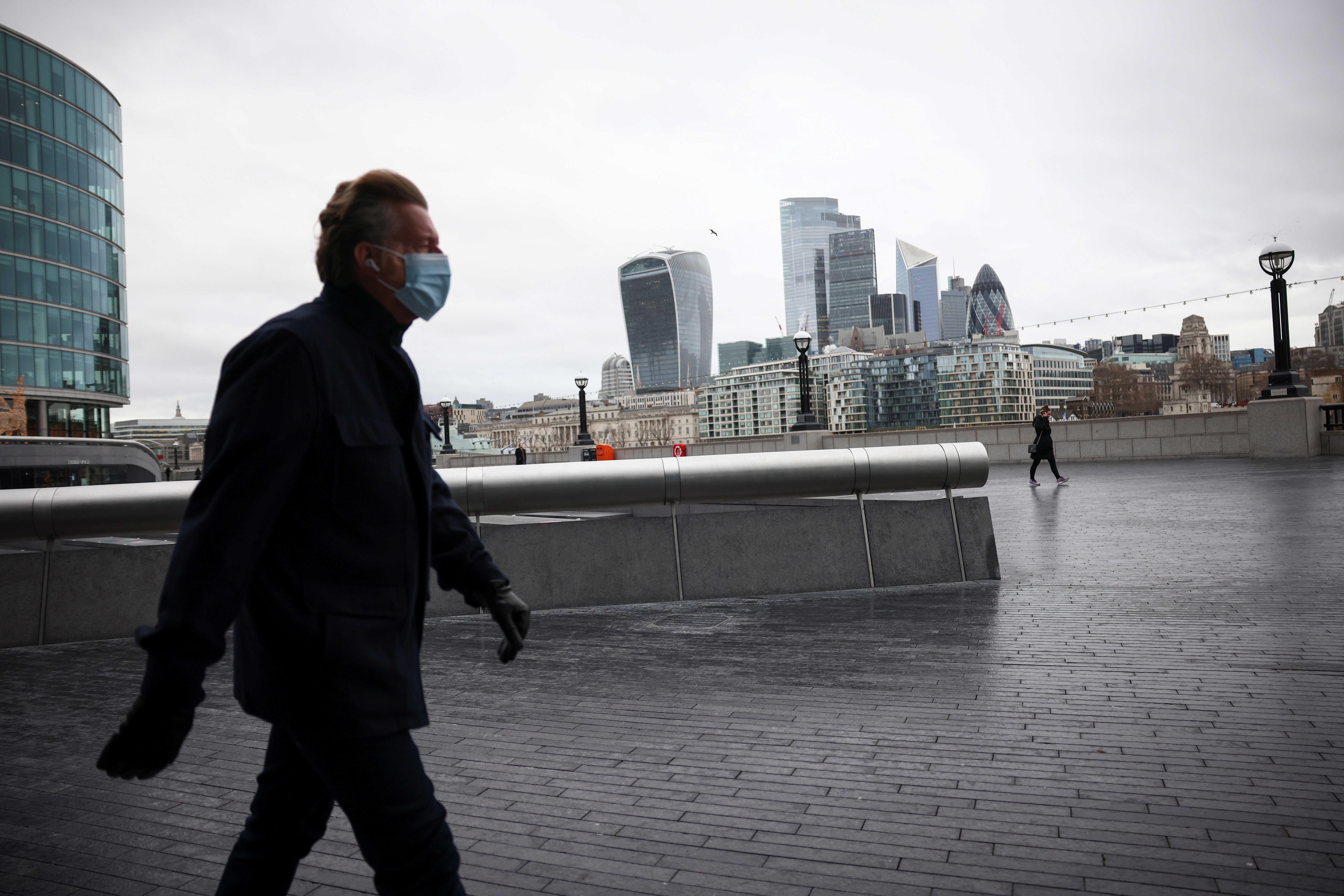 People walk at the South Bank of the River Thames, with the financial district in the background, amid the coronavirus disease (COVID-19) outbreak, in London, Britain, January 5, 2021. REUTERS/Henry Nicholls