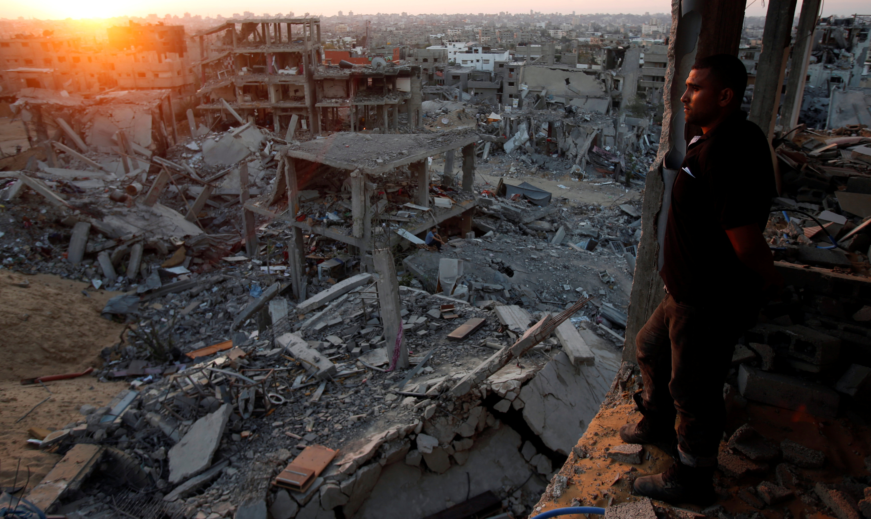 A Palestinian man looks out of his heavily damaged house at neighbouring houses which witnesses said were destroyed during the Israeli offensive, in the east of Gaza City September 3, 2014.   REUTERS/Suhaib Salem